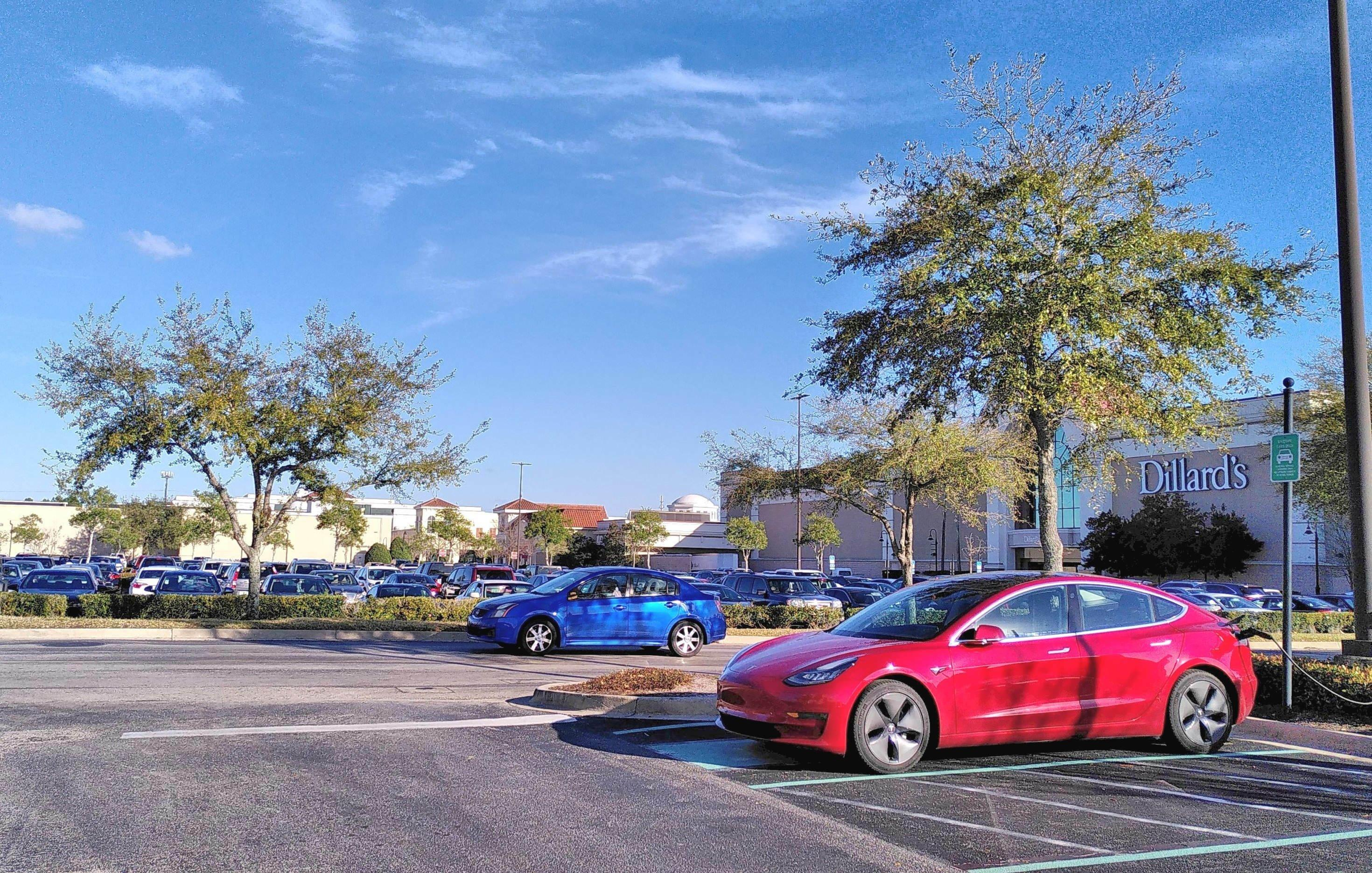 Ein roter Tesla steht auf einem Parkplatz.
