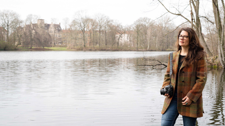 Sibylle Grunze im Winter mit Fotoapparat am Ufer eines Sees.