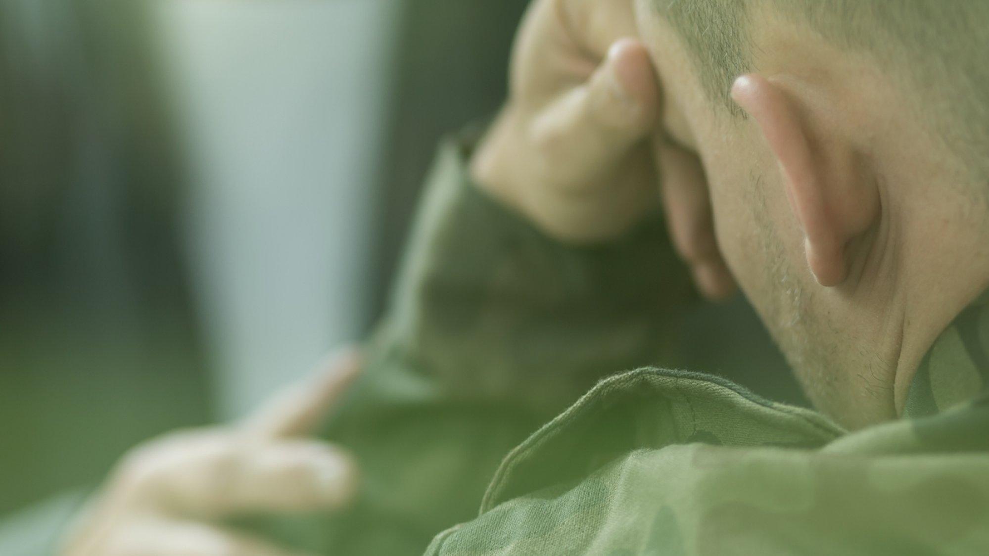Ein Soldat sitzt abgewandt von der Kamera und verbirgt sein Gesicht hinter den Händen.