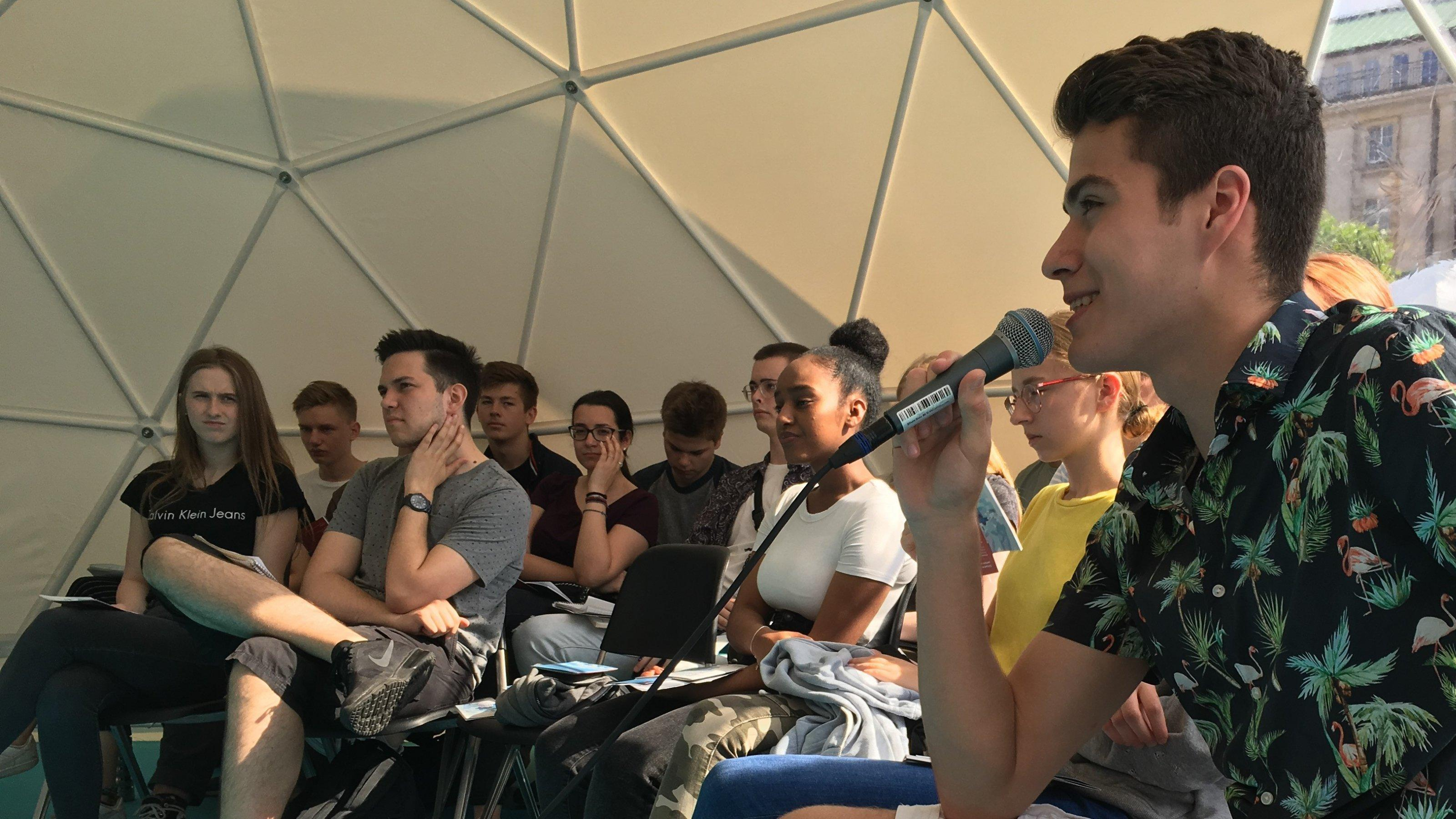 Ein junger Mann stellt im Zelt beim Sommer des Wissens eine Frage zu Crisprbabys.