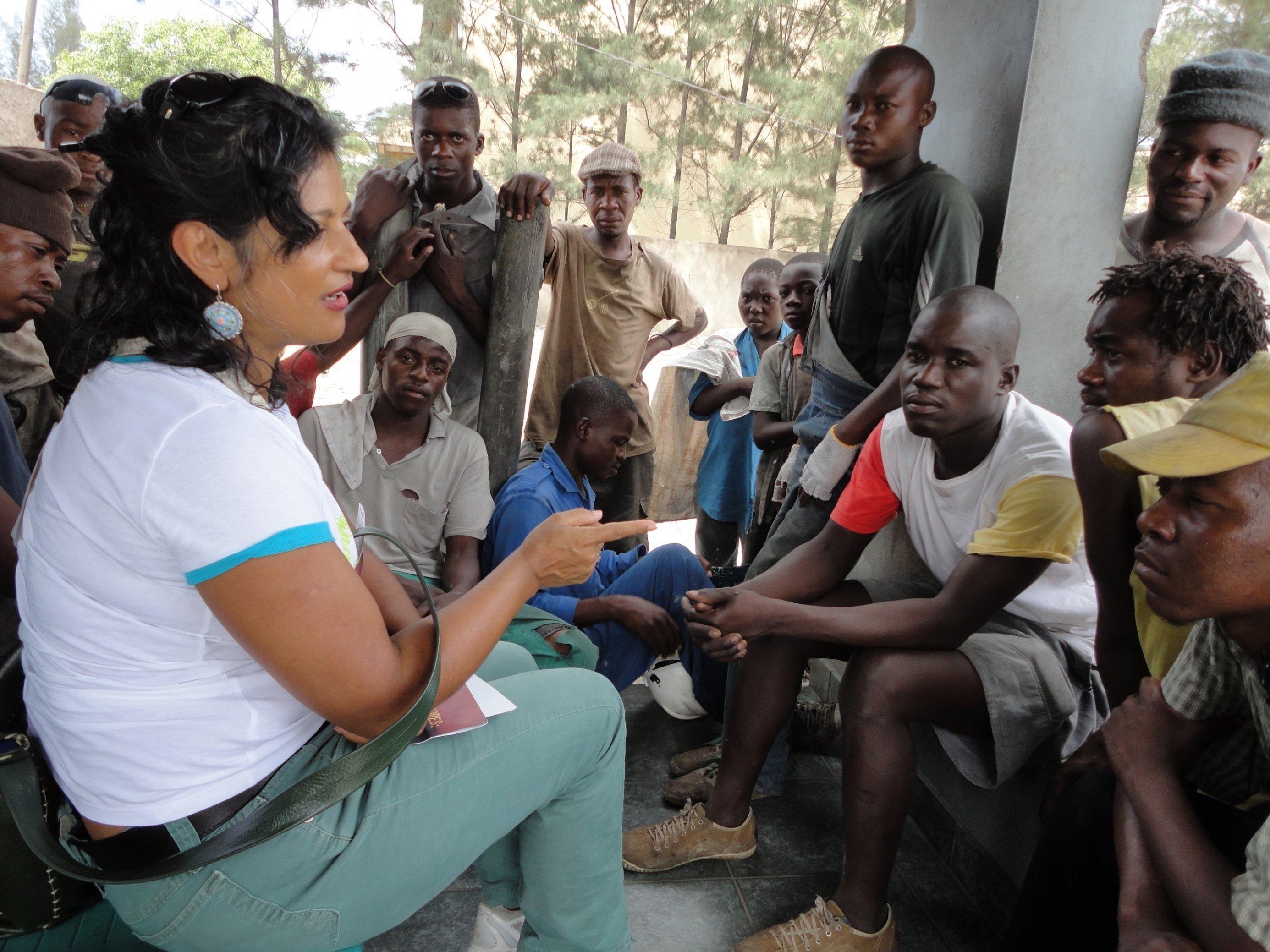 Soziologin Sonia Maria Dias sitzt vor einer Männergruppe und redet zu ihnen.