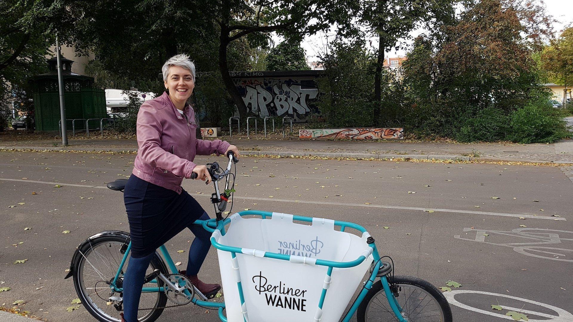 """Die Mobilitätsforscherin Sophia Becker steht mit einem Lastenrad auf einer zweispurigen Straße. Das Lastenrad hat einen türkisfahrbenenn Rahmen und vor dem Lenker eine weiße Box. In türkisfarbener Schrift  steht """"Berliner Wanne"""" auf der Lastenradbox."""