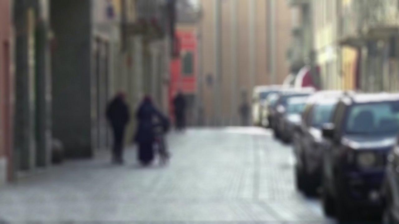 Das Bild ist unscharf und zeigt eine Straße in der links zwei Fußgänger laufen, einer von ihnen schiebt sein Fahrrad, rechts parken Autos