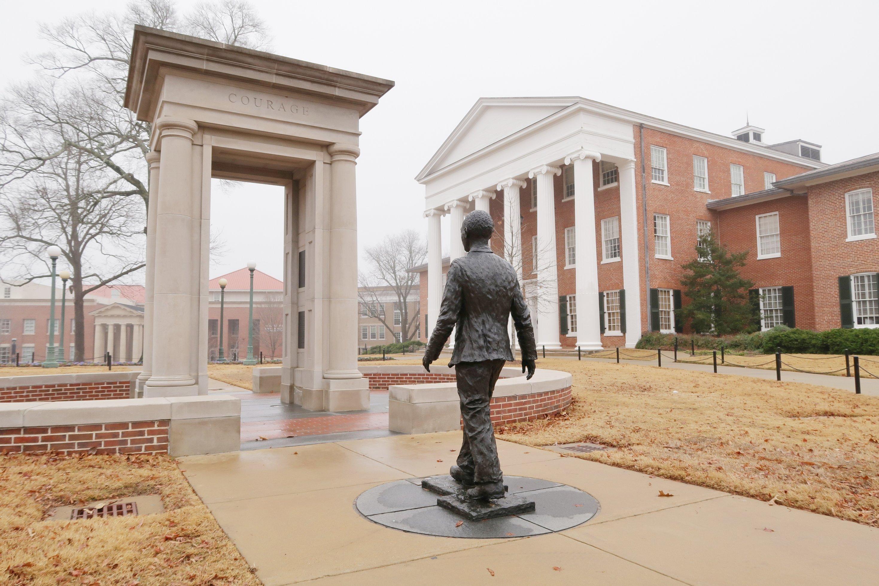 Statue eines Menschen vor einem Torbogen
