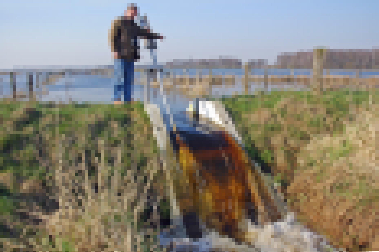 Heinrich Belting, Leiter der Naturschutzstation Dümmer, öffnet einen Stauwehr. Das Wasser fließt auf eine Wiese.