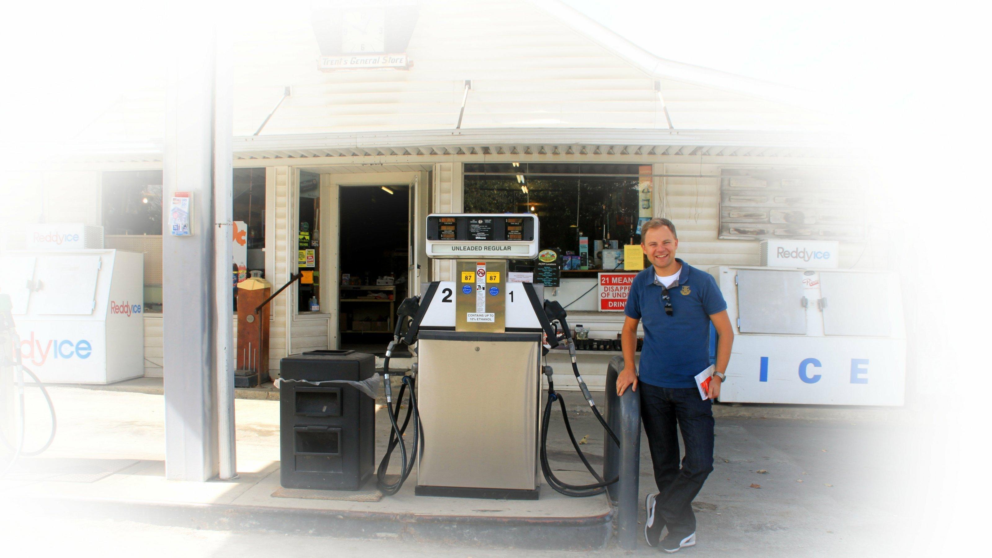 Ein junger Mann steht vor einer Tankstelle
