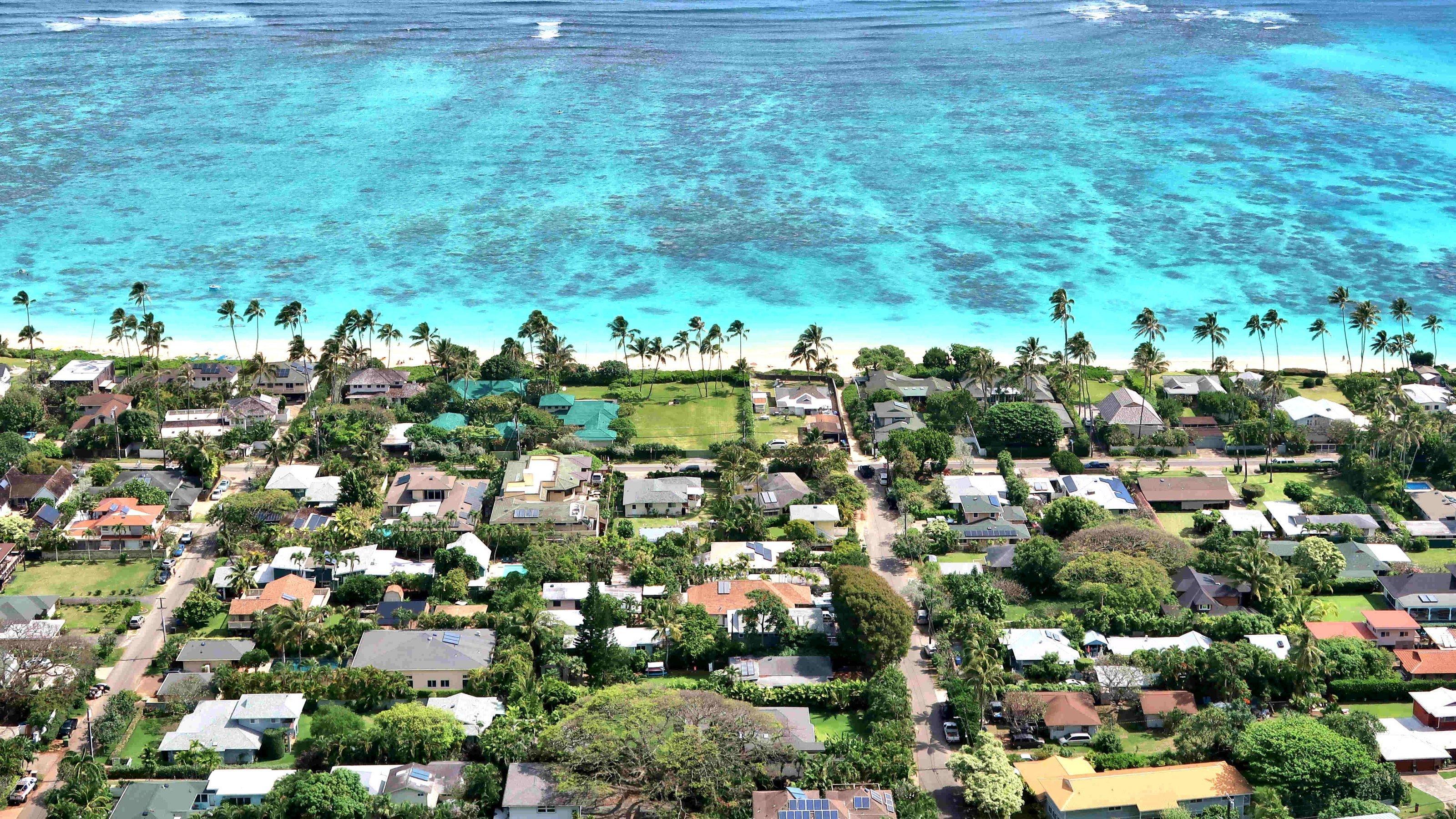 Vogelperspektive auf begrünten Wohnanlagen und Palmen am blauen Meer.