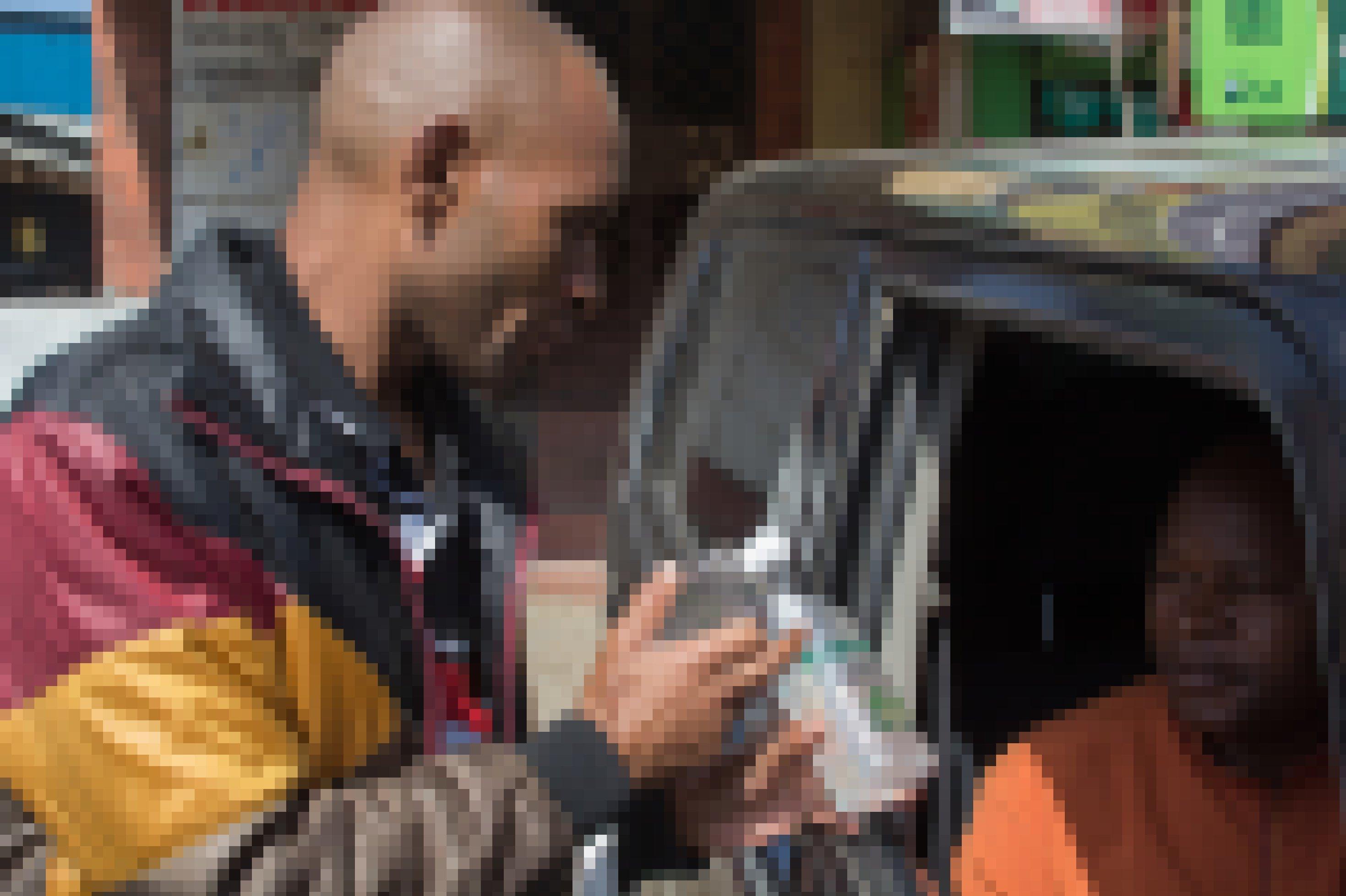 Ein Strassenhändler hält eine Flasche Desinfektionsmittel in ein offenes Autofenster