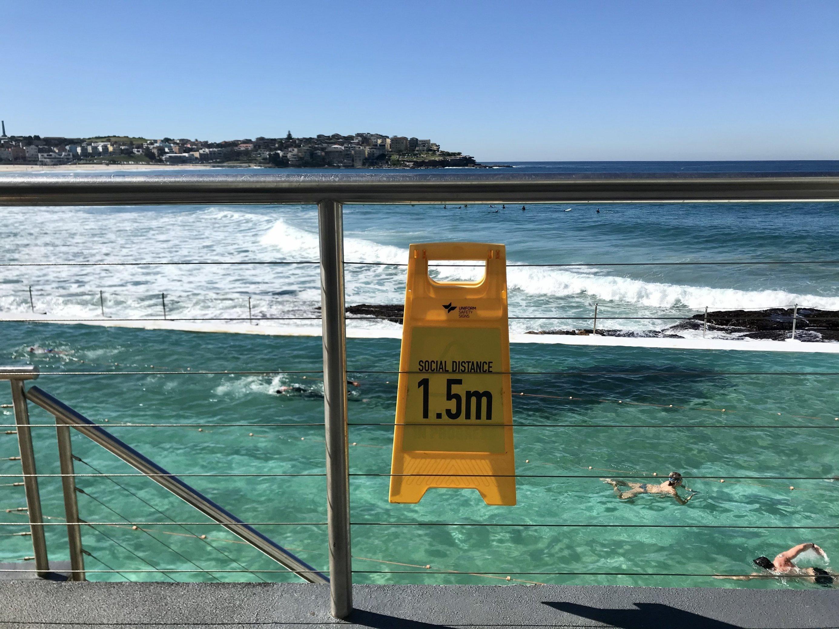 Im Meeresschwimmbad 'Icebergs' in Sydneys Strandvorort Bondi Beach ziehen Krauler ihre Bahnen. Ein Schild erinnert daran, 1,5Meter Abstand zu anderen Menschen zu halten. In der letzten Juniwoche geht auch das Meeresschwimmbad wieder in den Lockdown.