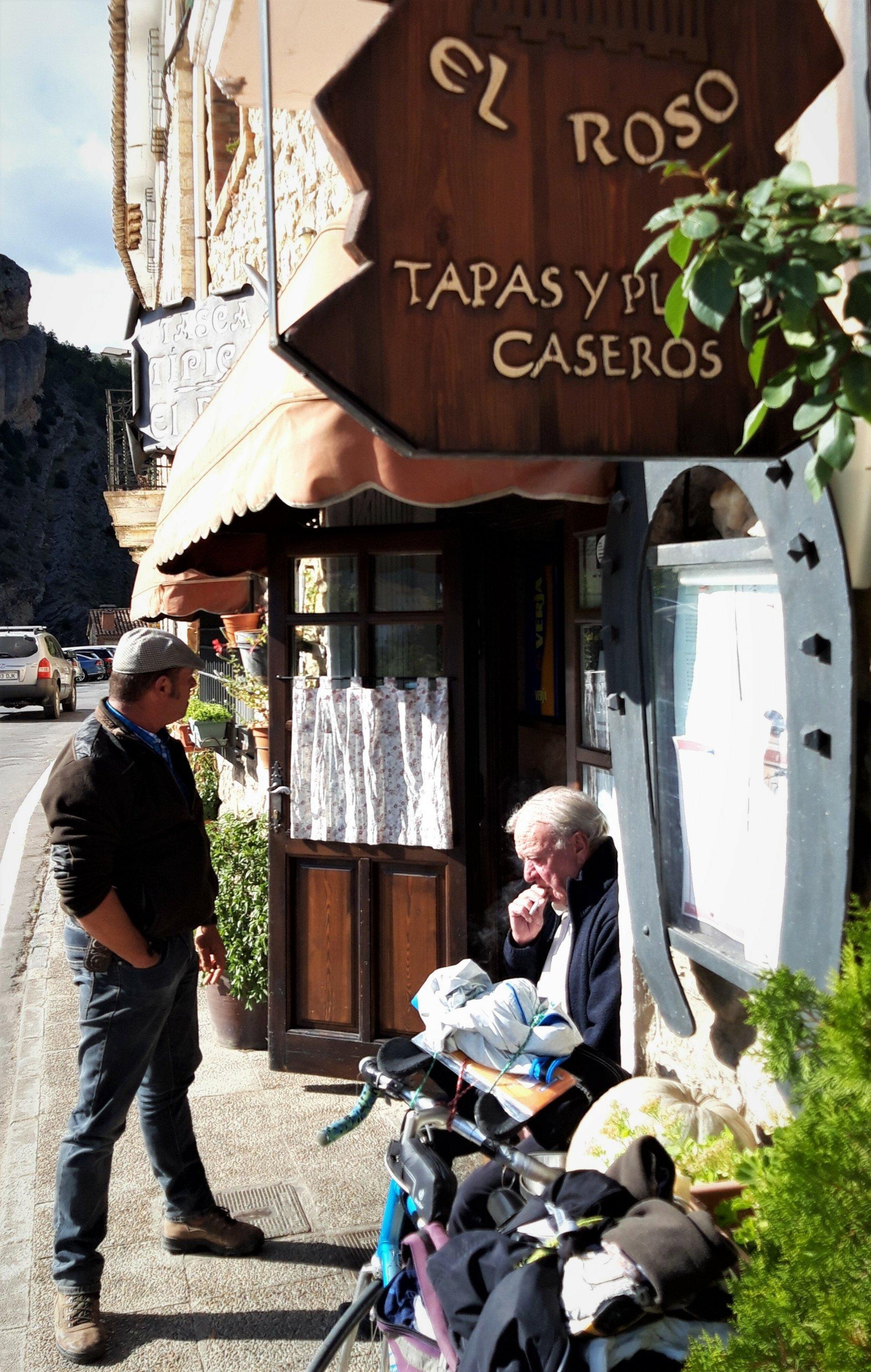 Zwei Männer vor der Taberna El Roso, einer stehend, der andere sitzend.
