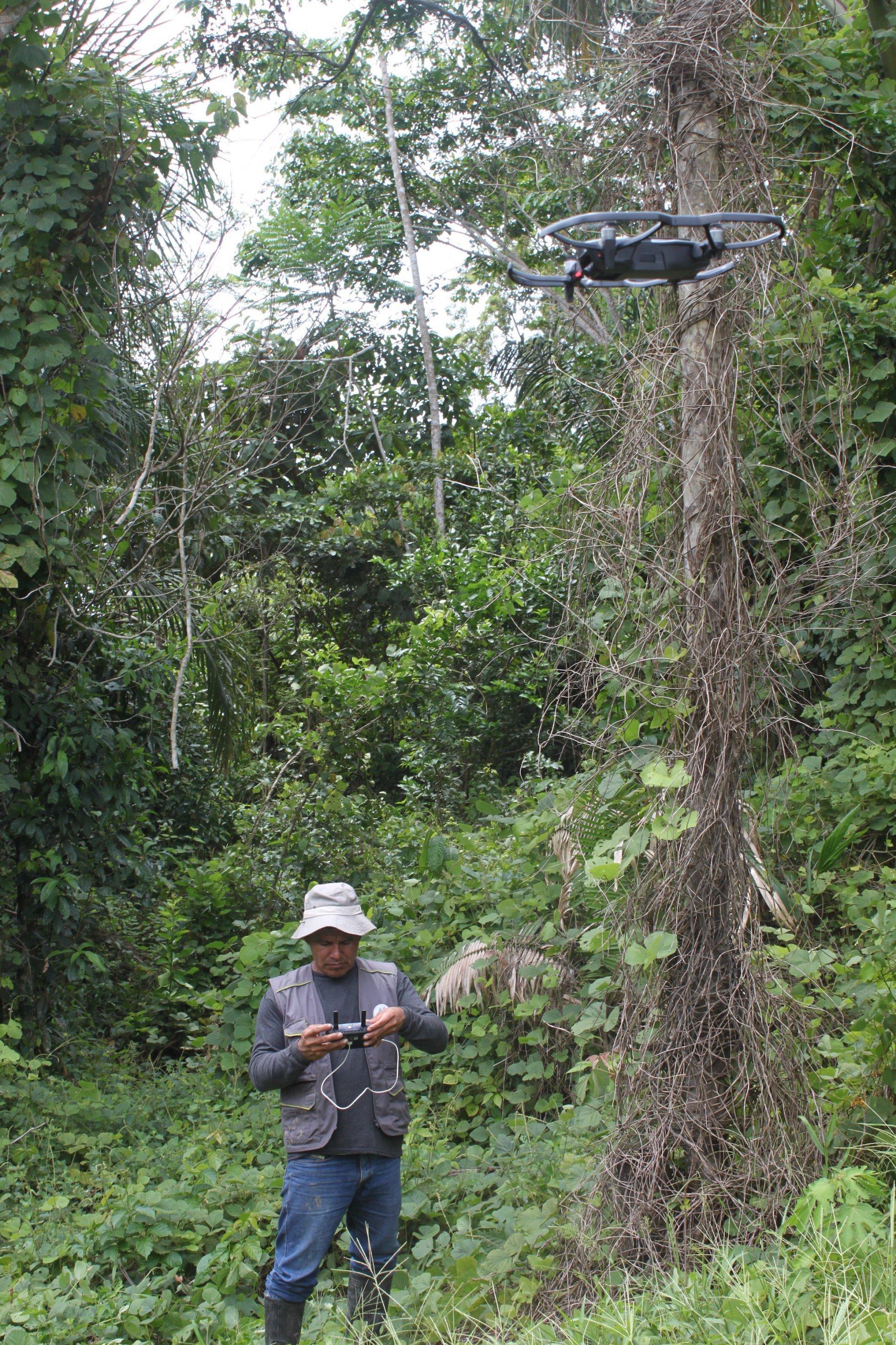 Ein Mann mit Trapperjacke und Hut bedient eine Drohne. Der Mann steht inmitten eines Gebüschs, ist von hohen Bäumen und Gebüsch umgeben.