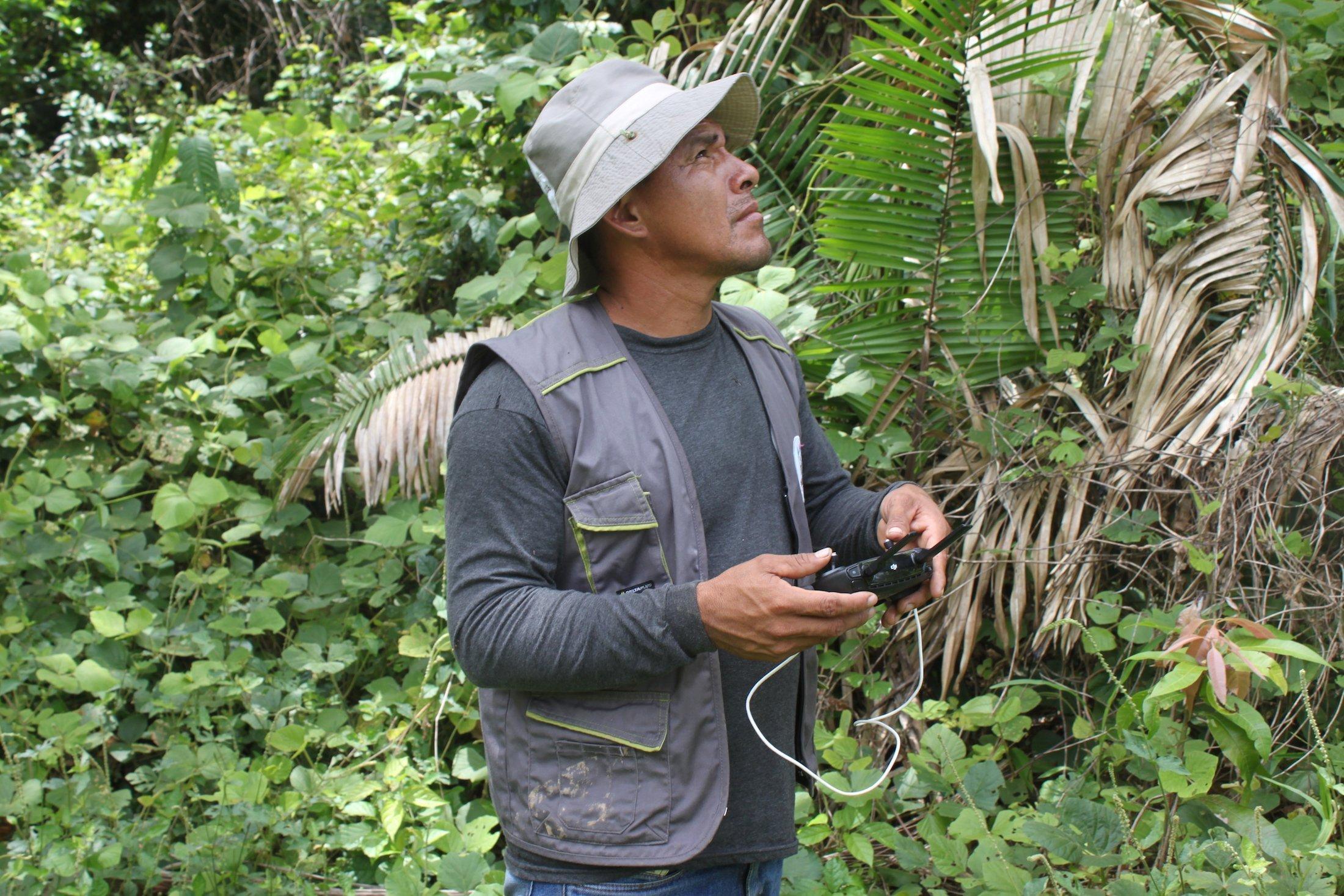 Ein indigen aussehender Mann steht im Regenwald und steuert eine Drohne.