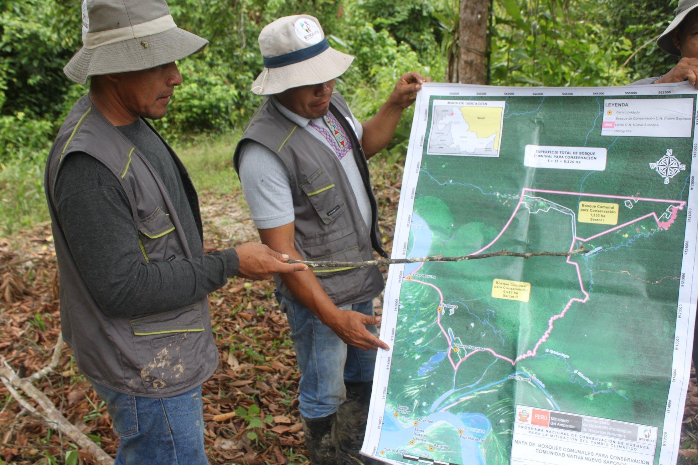 Zwei indigen aussehende Männer mit Trapperhut und Outdoor-Kleidung schauen auf eine grosse Landkarte ihres Gemeindegebietes.