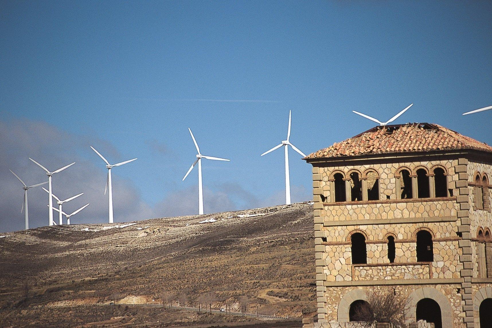Im Vordergund ein verwaistes Steinhaus, im Hintergrund ein Bergrücken mit Windkraftanlagen.