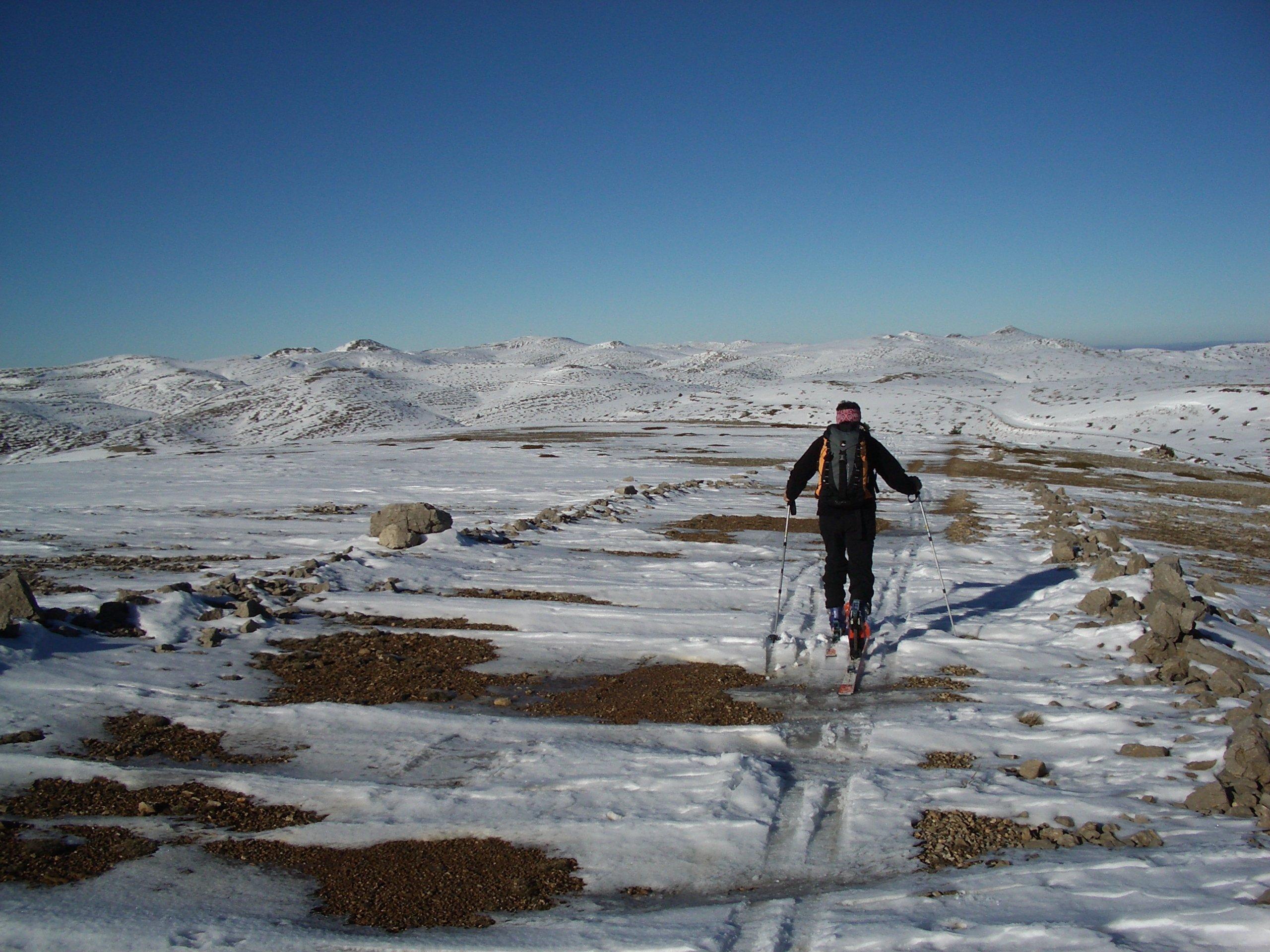 Ein Skitourengeher bewegt sich über die Schneereste auf einer Gebirgsanhöhe.