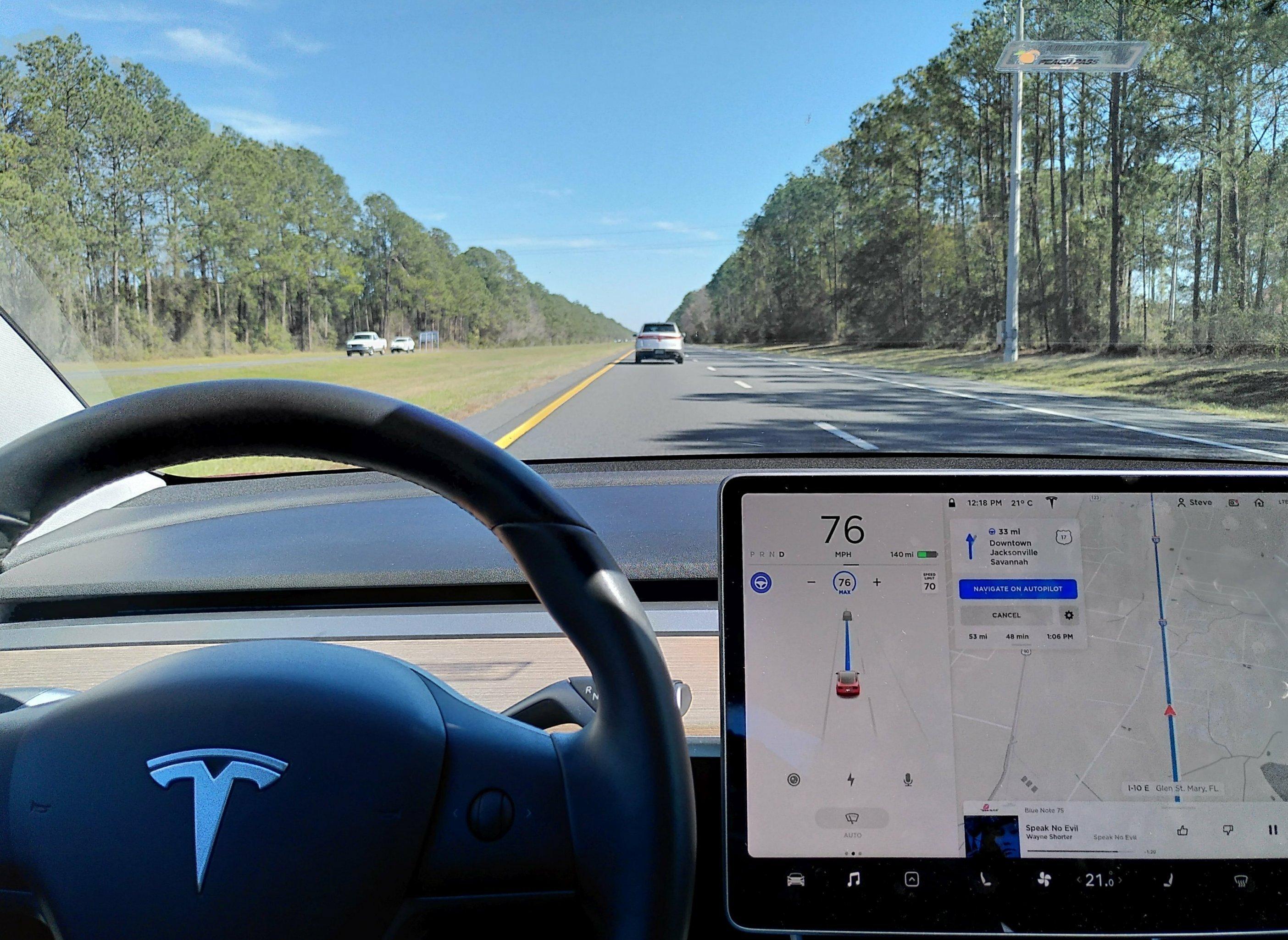 Blick aufs Armaturenbrett eines Teslas während der Fahrt.