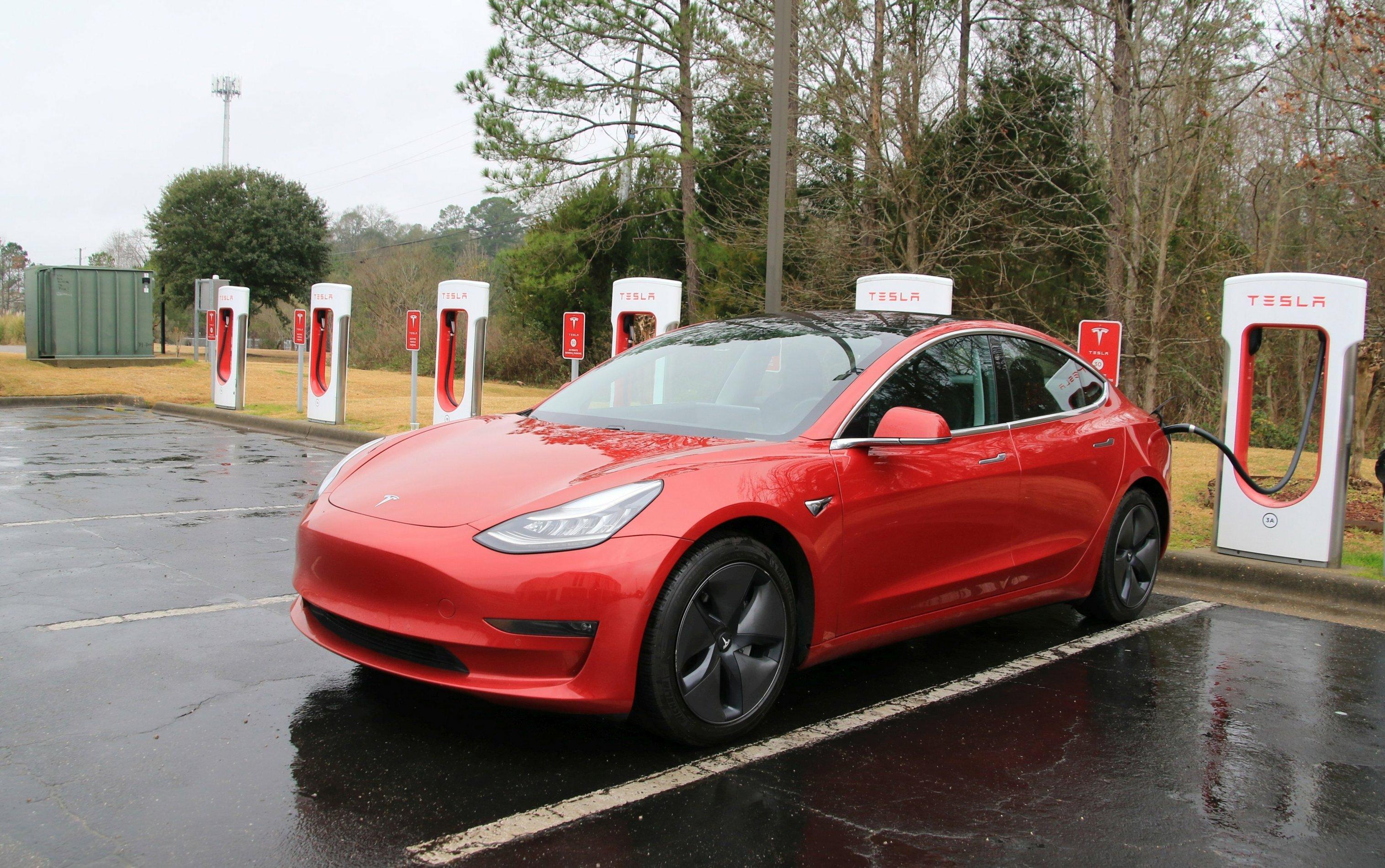 Ein Tesla ist an einer Ladesäule angeschlossen.