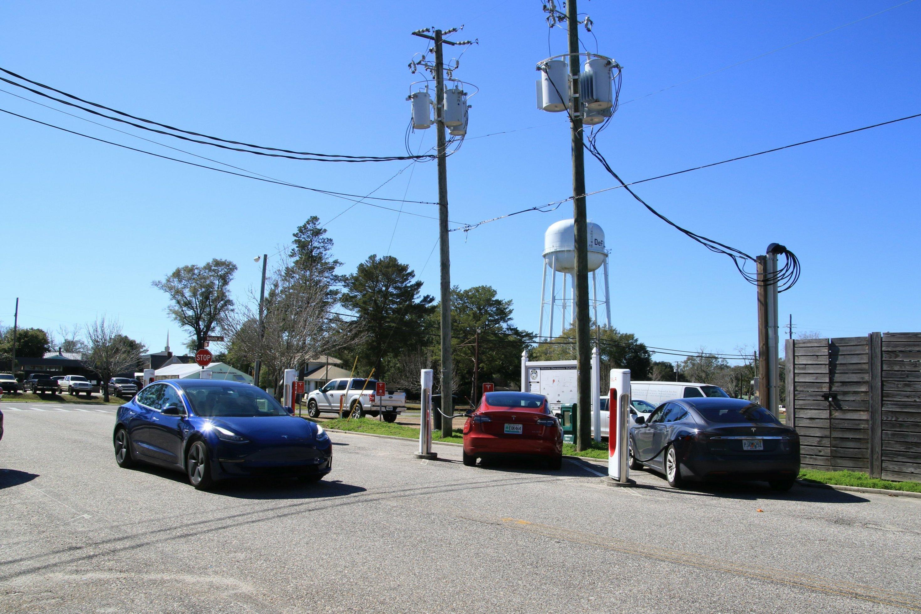 Ein Auto fährt über eine Straße, im Hintergrund parken zwei weitere Autos und zapfen Strom.