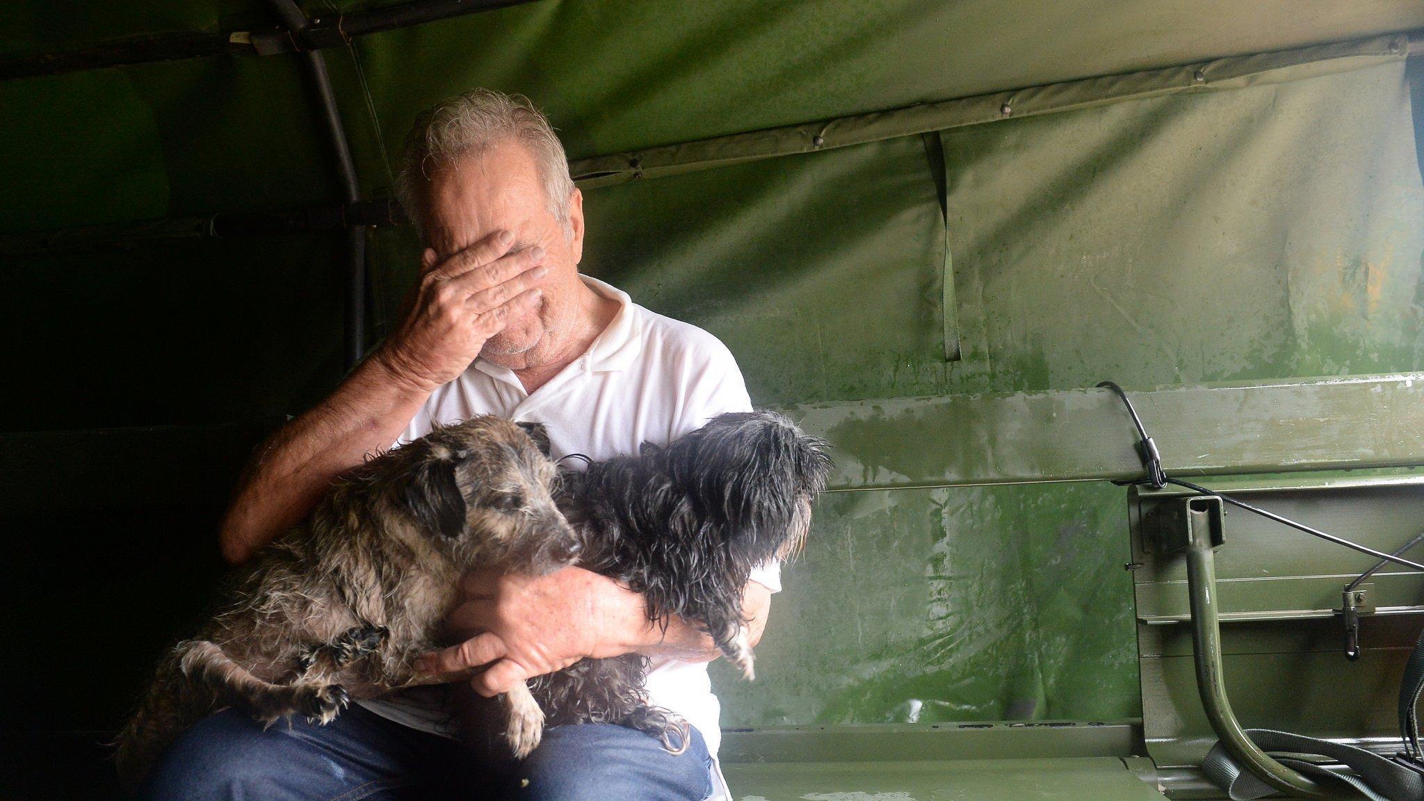 """Ein älterer Mann sitzt auf einer Pritsche in einem Lastwagen. Er hat zwei kleine Hunde im Arm und hält sich die Hand vor die Augen. Er macht einen verzweifelten Eindruck. Seine Kleidung ist durchnässt. Die Texas National Guard war ihm zur Hilfe gekommen, als Hurrikan """"Harvey"""" im August 2017sein Stadtviertel in Houston überschwemmte."""
