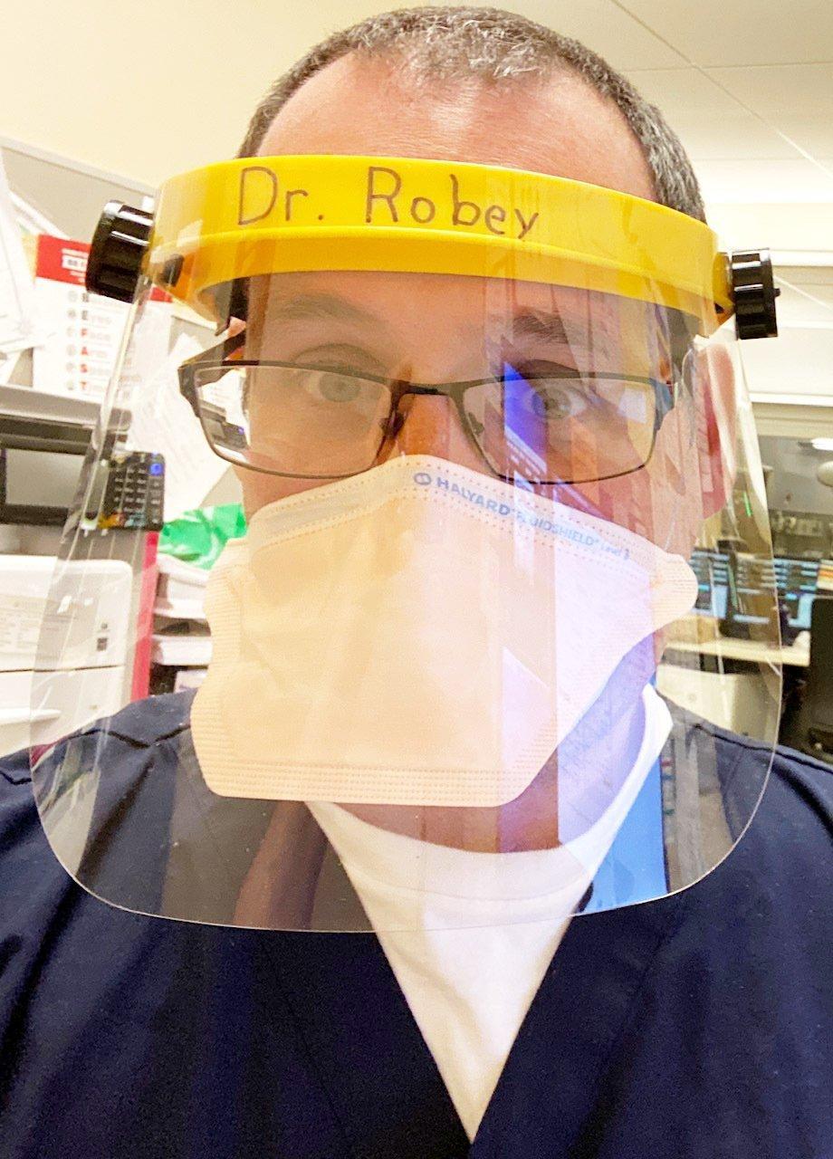 Nahaufnahme eines Arztes mit Mundschutz und Gesichtsvisier