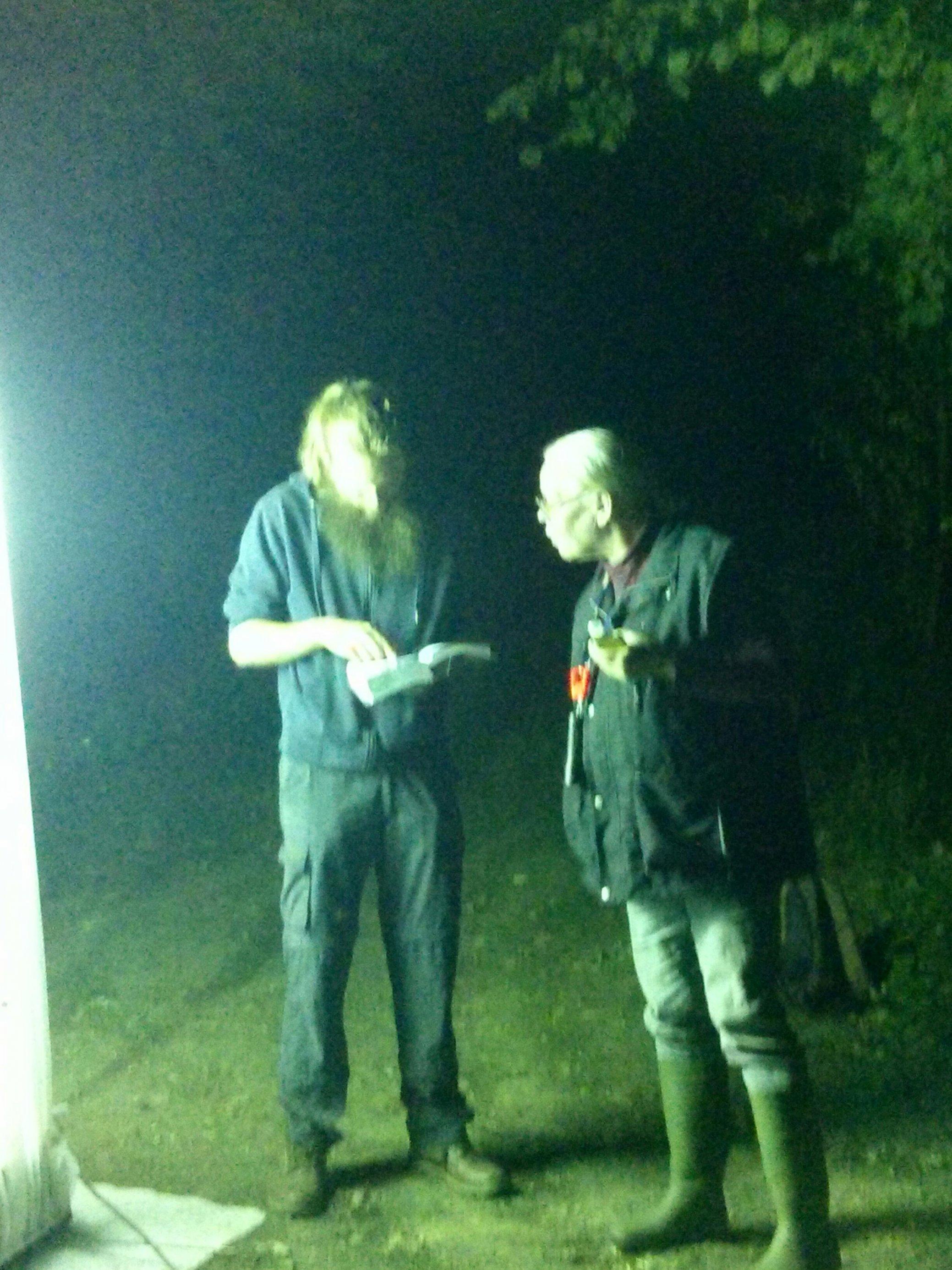 """Die Nachtfalterexperten Birgitt Piepgras und Timo Zeimet beugen sich im Schein eines """"Leuchtturms"""" zum Anlocken von Fluginsekten über einen Falter, den sie zwecks Bestimmung für kurze Zeit in ein Plastikgefäß gesteckt haben."""