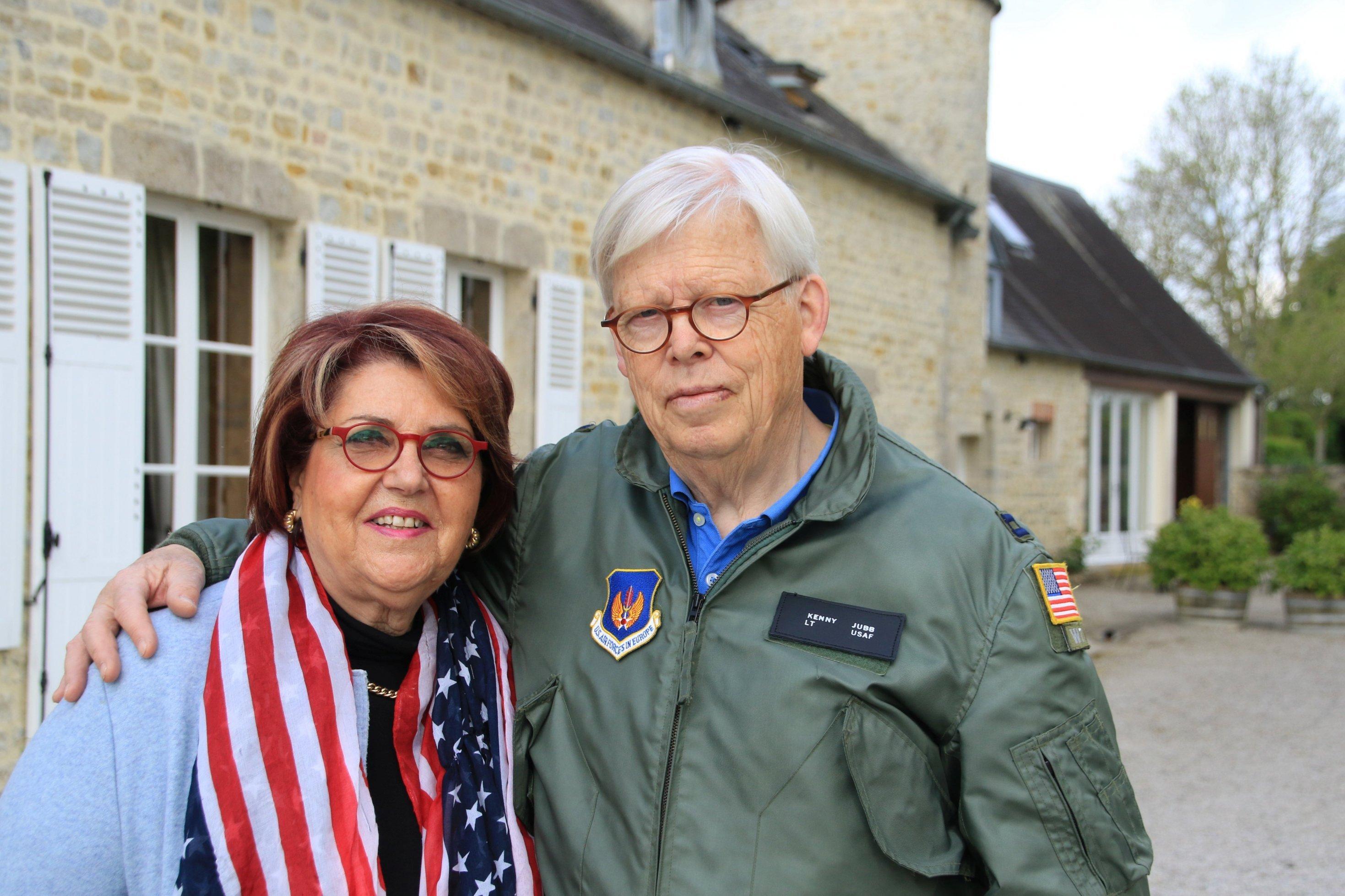 Ein älteres Ehepaar, er trägt Bomberjacke, sie einen Schal mit der US-Flagge