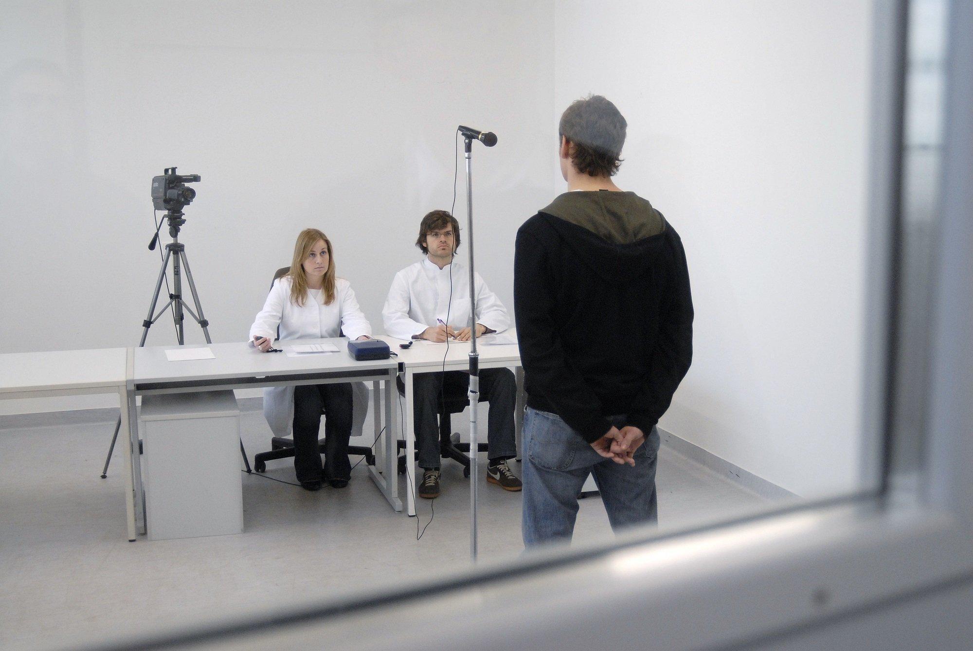 Ein Mann steht vor zwei sitzenden Menschen, die ihn neutral betrachten.
