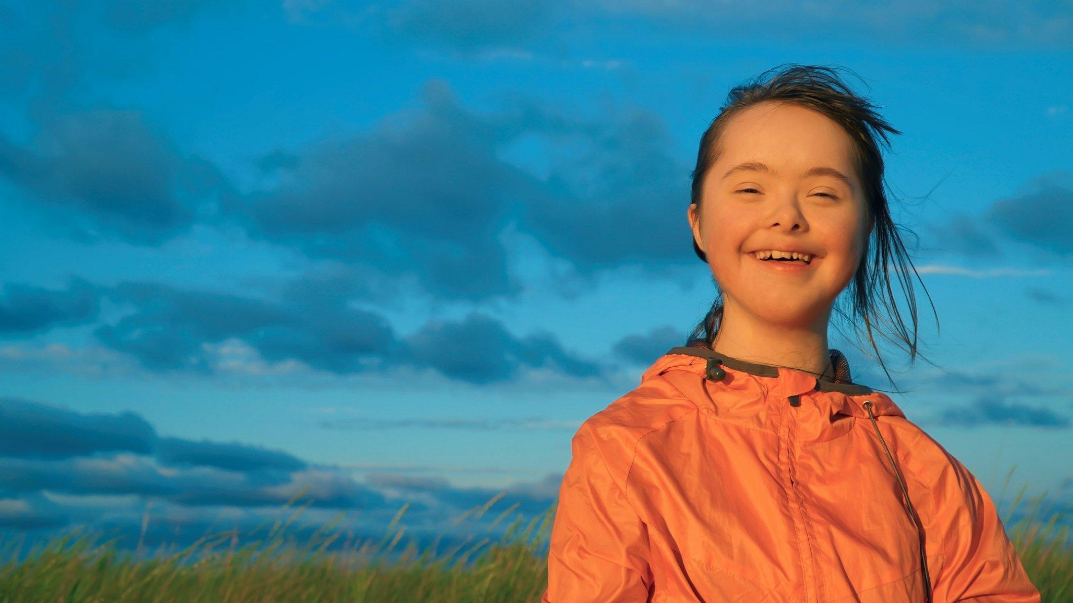 Ein fröhliches Mädchen mit Down-Syndrom lachend auf einer Wiese  vor blauem Himmel