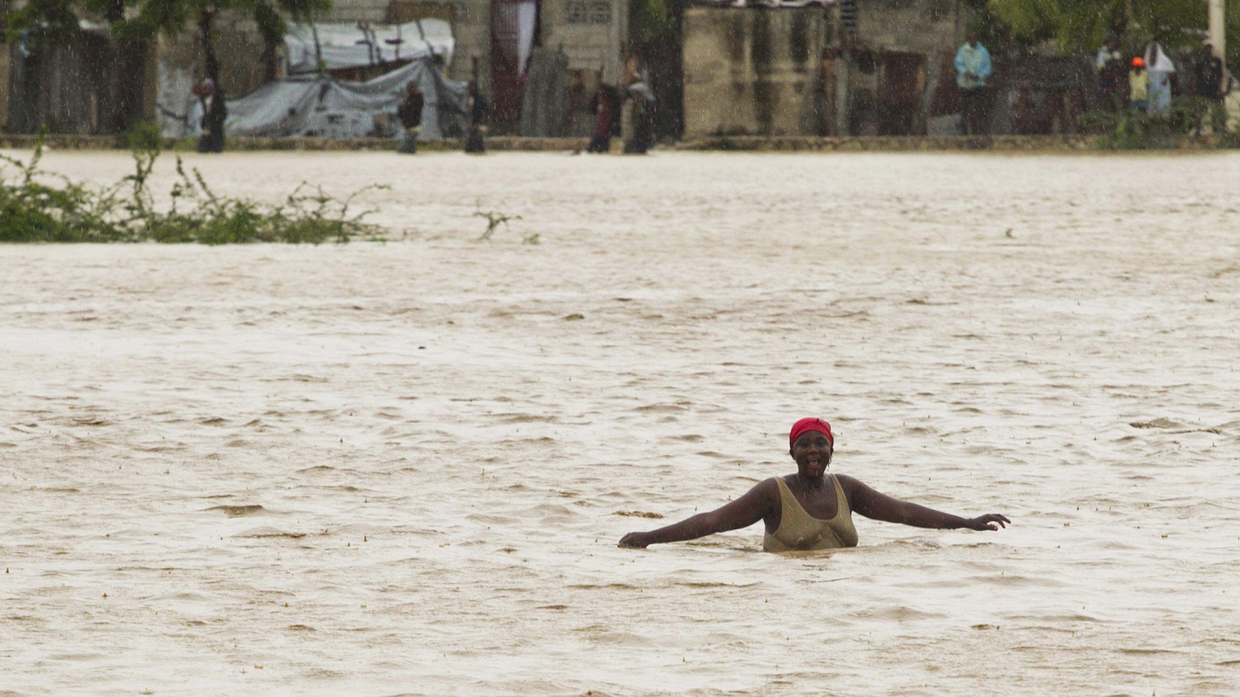 Eine Frau watet durch eine brusthohe Wasserfläche. Als der Tropensturm Isaac 2012Haiti erfasste, da liefen schnell die tieferliegenden Teil der Hauptstadt Port-au-Prince voll – wo auch immer noch viele Opfer des Erdbebens zwei Jahre zuvor in Lagern hausten.