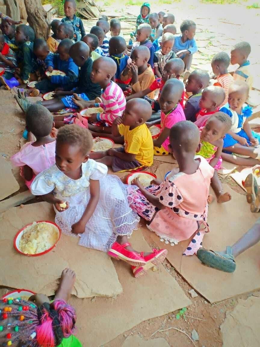 Massai-Kinder sitzen auf dem Boden, sie werden von Ellie Modesta unterrichtet.