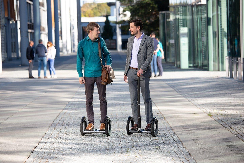 Zwei Männer stehen jeweils auf einem ausklappbaren E-Floater, der so ähnlich aussieht wie ein Segway – aber ohne Stange.