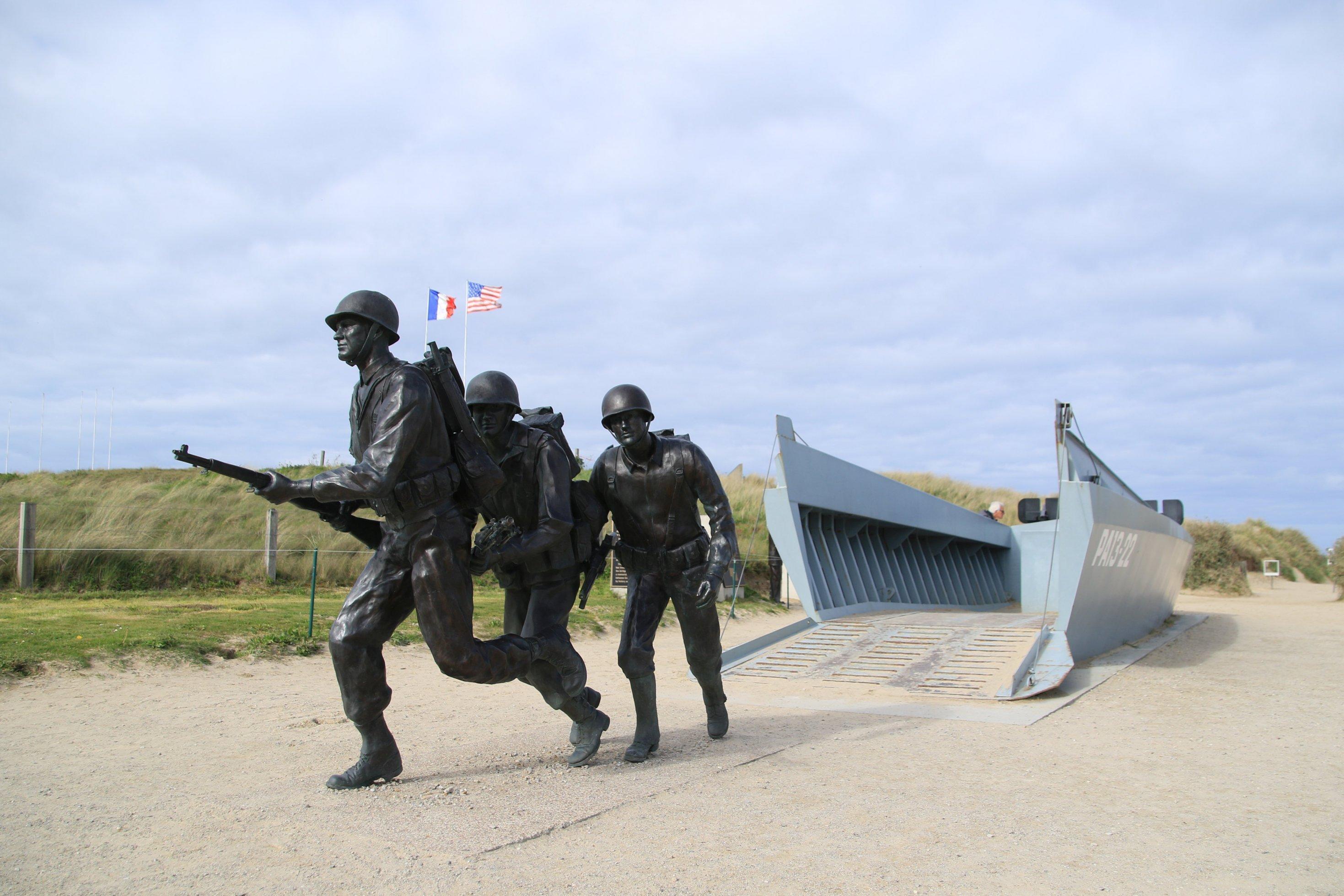 Eine Skulptur zeigt Soldaten, die aus einem Schiff springen.