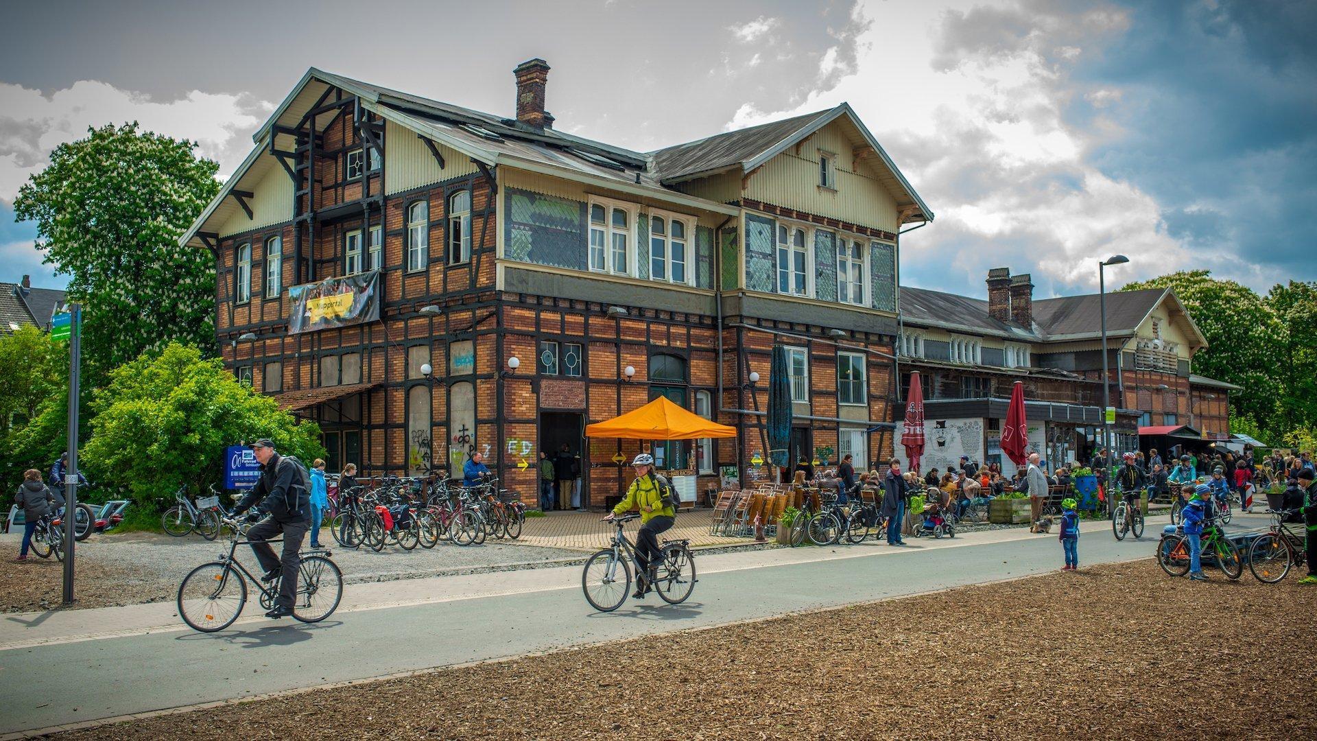 Ein Fachwerkhaus, vor dem Fahrräder stehen und an dem Radfahrer vorbeikommen.