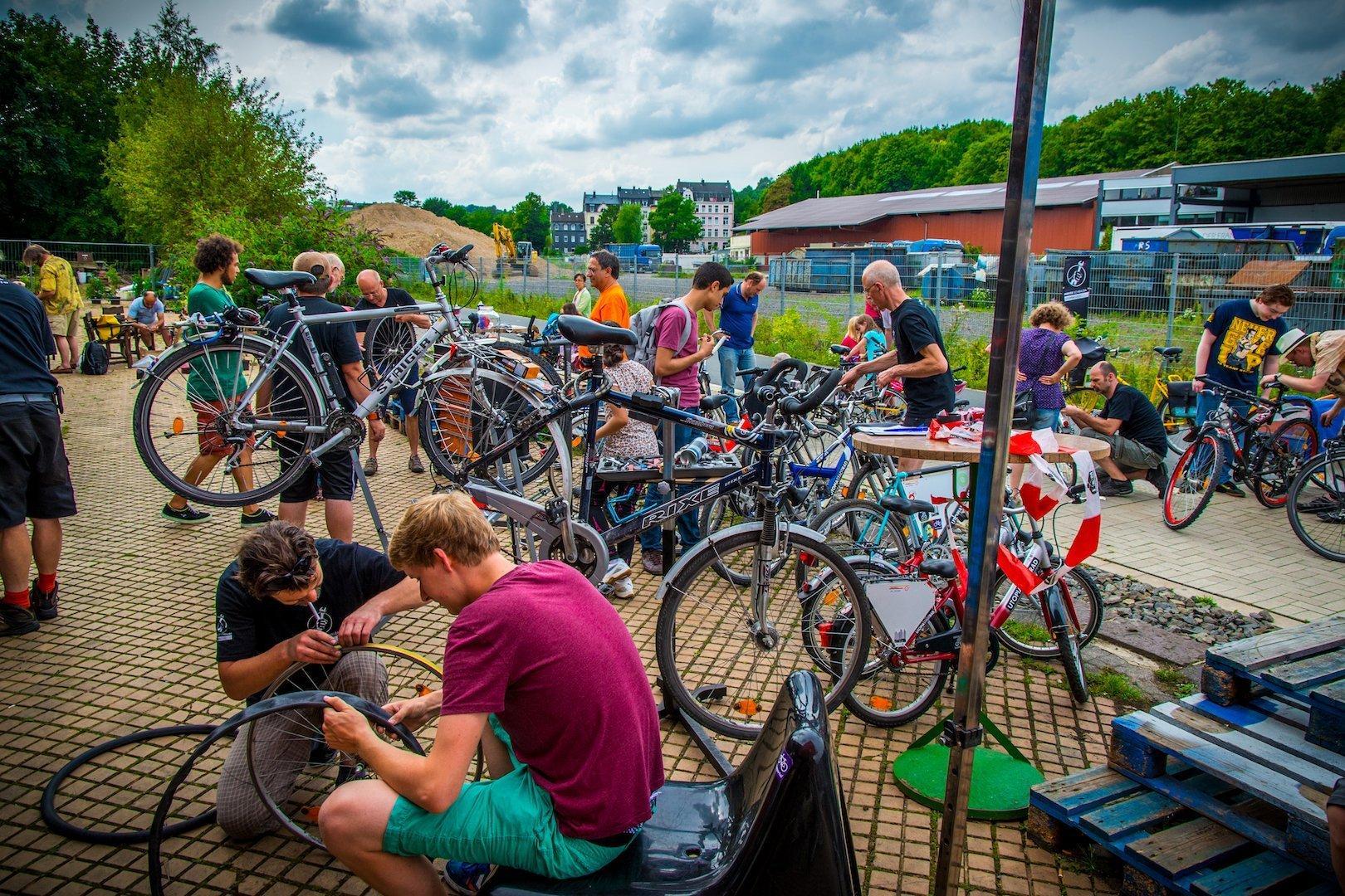 Viele Menschen auf einem Hof, die Fahrräder reparieren und sich dabei unterstützen.
