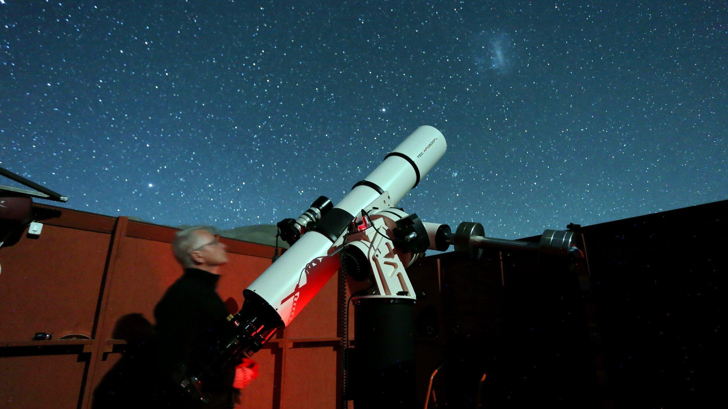 Ein Mann steht neben einem großen Fernrohr in einer Schutzhütte mit geöffnetem Dach und fotografiert den nächtlichen Sternenhimmel