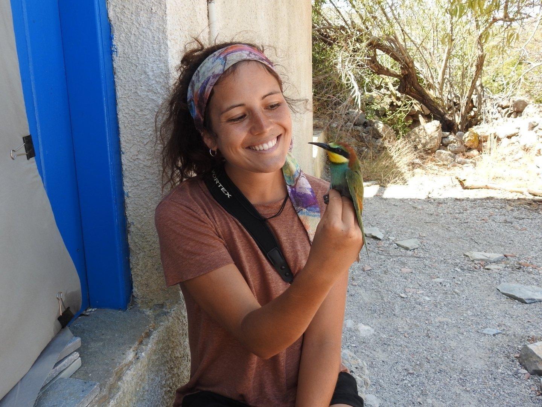 Die junge Ornithologin Verena Rupprecht sitzt vor einer Hütte und hält einen bunten Vogel in der Hand, einen Bienenfresser