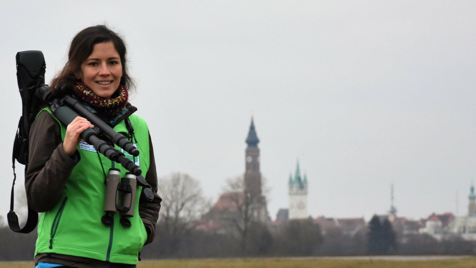 Eine junge Ornithologin steht auf einer Wiese, auf der Schulter trägt sie ein Stativ mit einem Fernrohr. Sie lächelt in die Kamera.