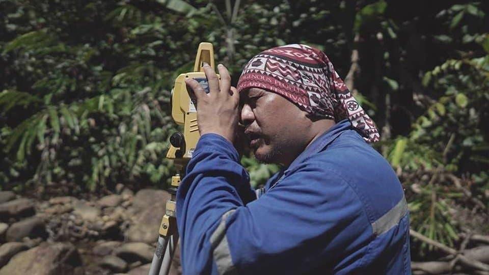 Ein Mann im Blaumann mit einem bunten Tuch auf dem Kopf schaut nach links durch ein optisches Messinstrument. Im Hintergrund ist das üppige Grün eines tropischen Waldes zu sehen. – Die Fallhöhe bei einem kleinen Laufwasser-Kraftwerk bestimmt die Technik der Turbine. Adrian Lasimbang von der malaysischen Firma Tonibung vermisst darum die möglichen Führung von Rohren bei einem neuen Projekt.
