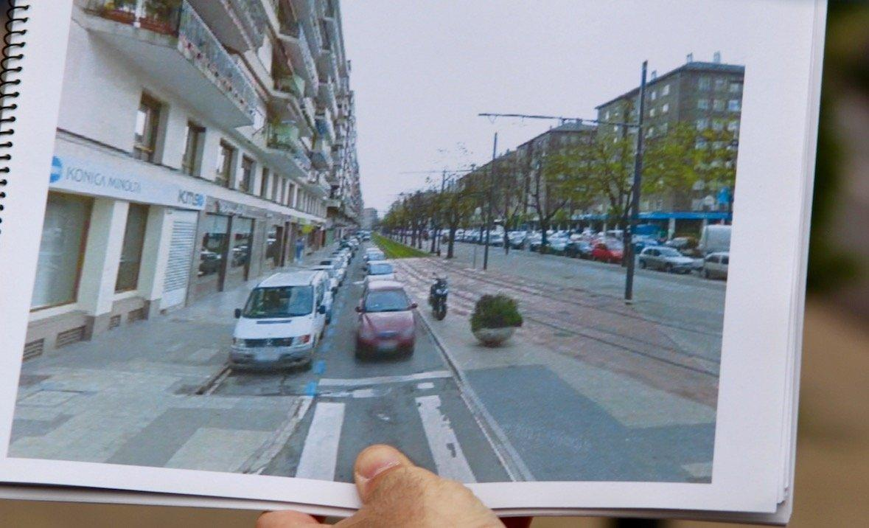 Nahaufnahme auf ein geöffnetes Buch, das von einer Hand gehalten wird. Die Doppelseite die Straße vor dem Umbau.