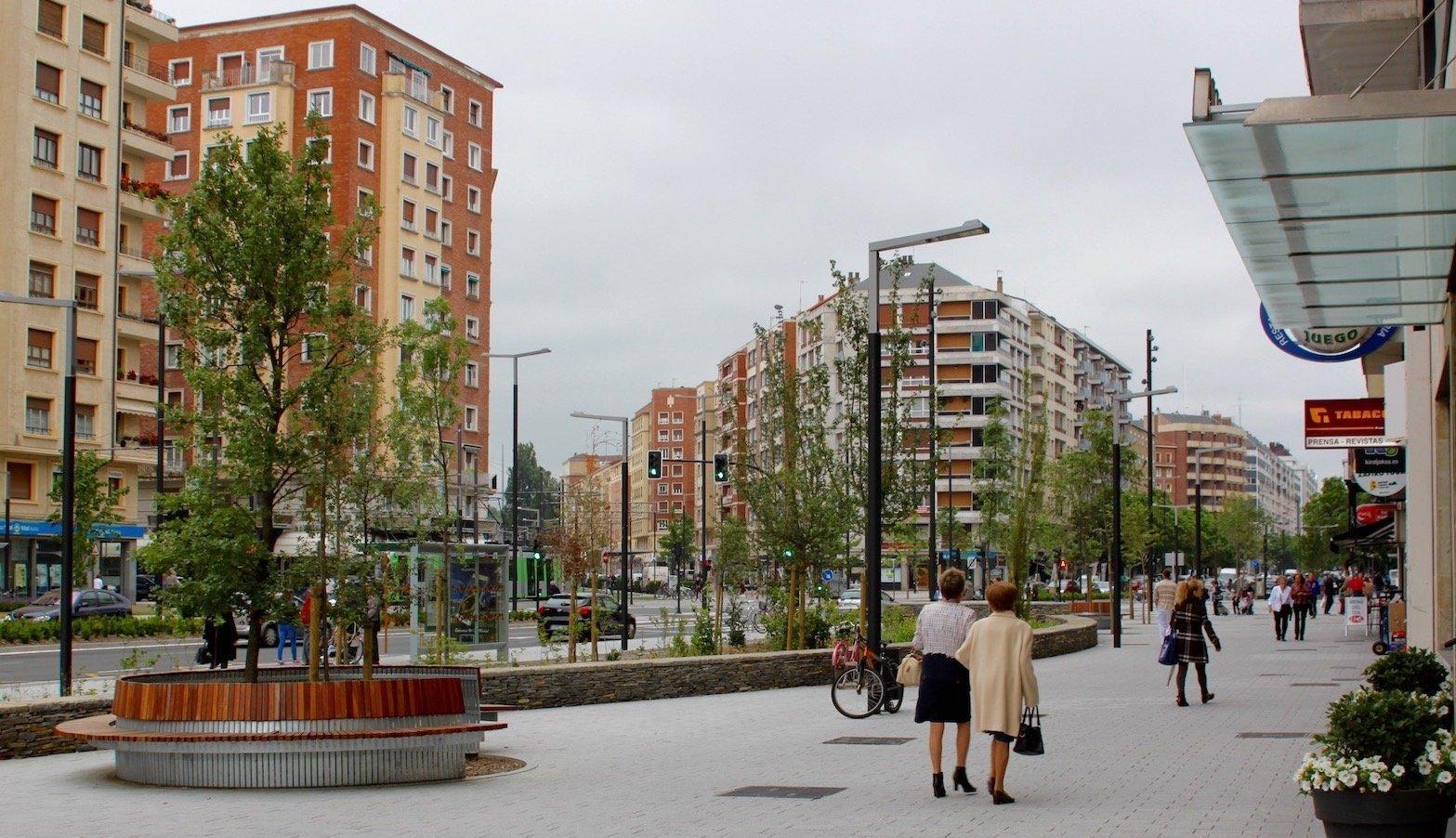 Ein Fußgängerzone, die umsäumt von Hochhäusern ist.