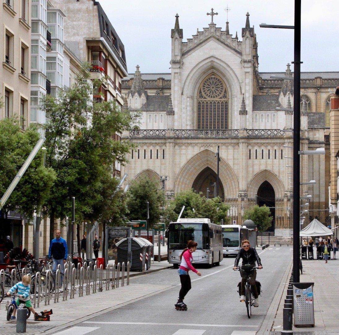 Blick auf eine Bushaltestelle mitten in der Stadt. Im Hintergrund ist eine Kathedrale zu sehen. Im Vordergrund ein Radfahrer und eine Skaterin.