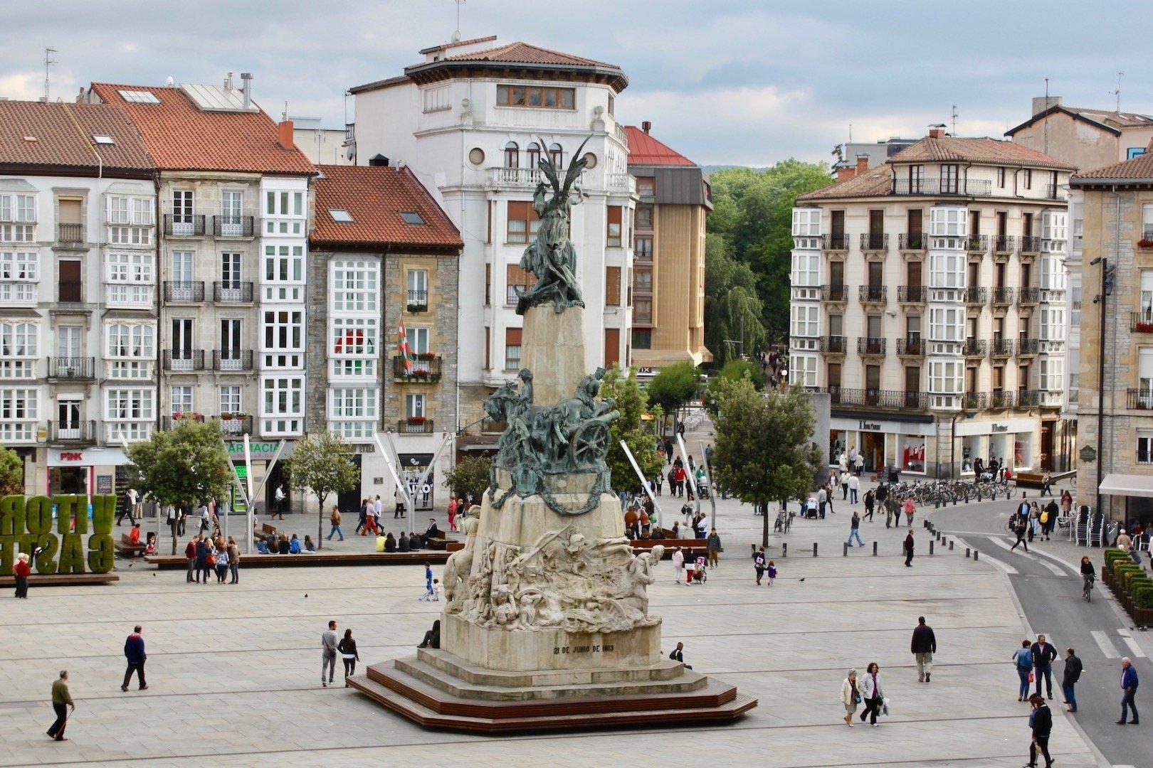 In der Mitte des Marktplatzes steht ein großer Brunnen. Viele Fußgänger sind zu sehen. Der Platz ist von Häusern umsäumt.