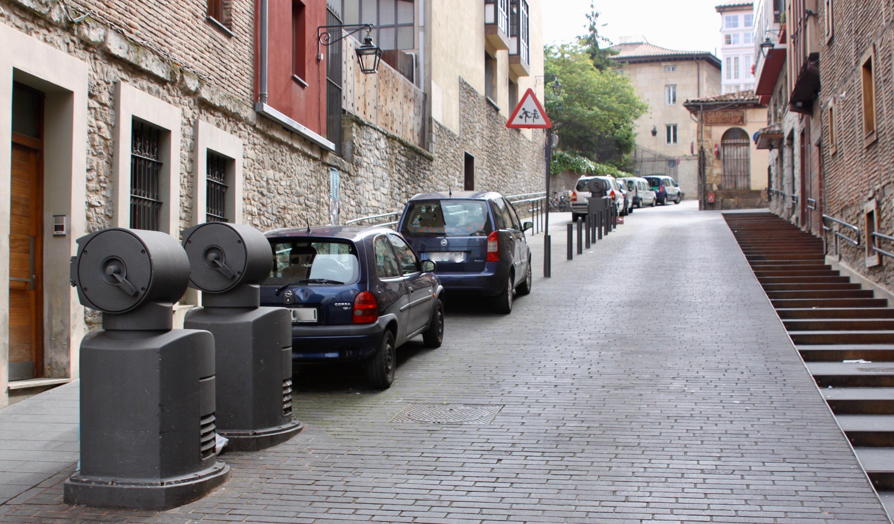 Eine kleine Gasse. Links stehen vor zwei Müllschluckern parkende Autos.