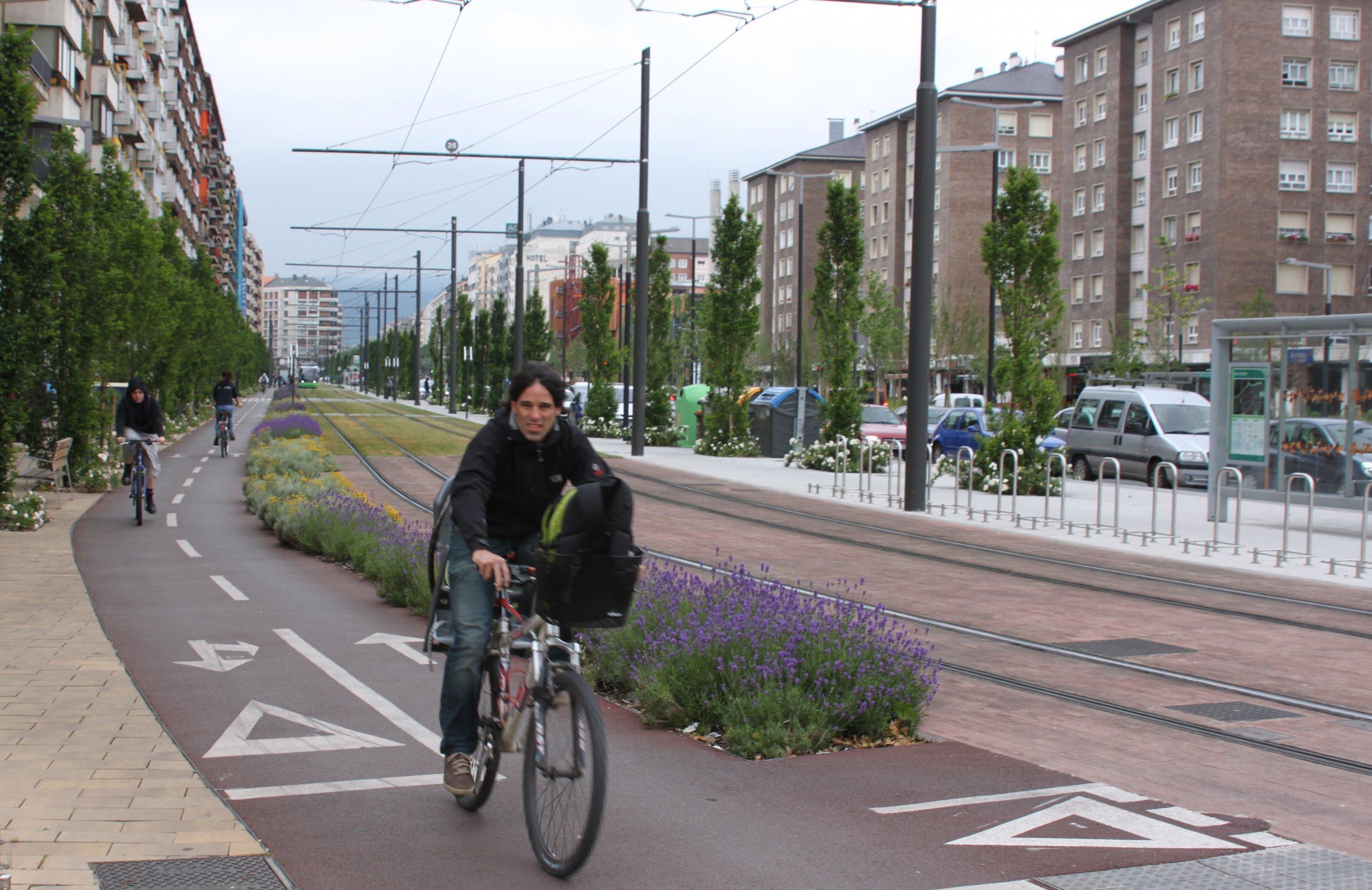 Eine Radfahrerin fährt auf einer Radspur neben Tramschienen. Hochhäuser sind an beiden Straßenseiten zu sehen.