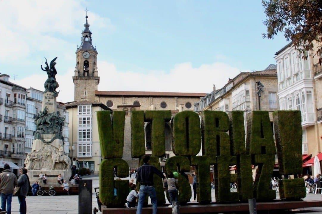 """Ein pompöses Gebäude mit Turm im Hintergrund. Davor steht der große Schriftzug """"Vitoria Gasteiz"""""""