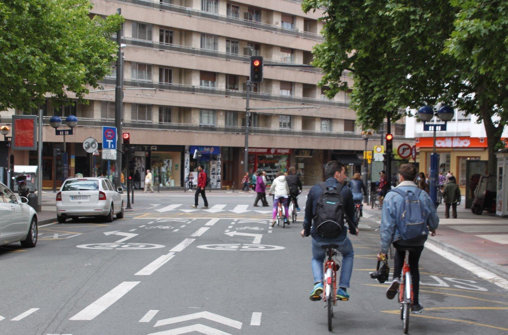 Radfahrer auf der Straße. Im Hintergrund sind Fußgänger und Hausfassaden zu sehen.