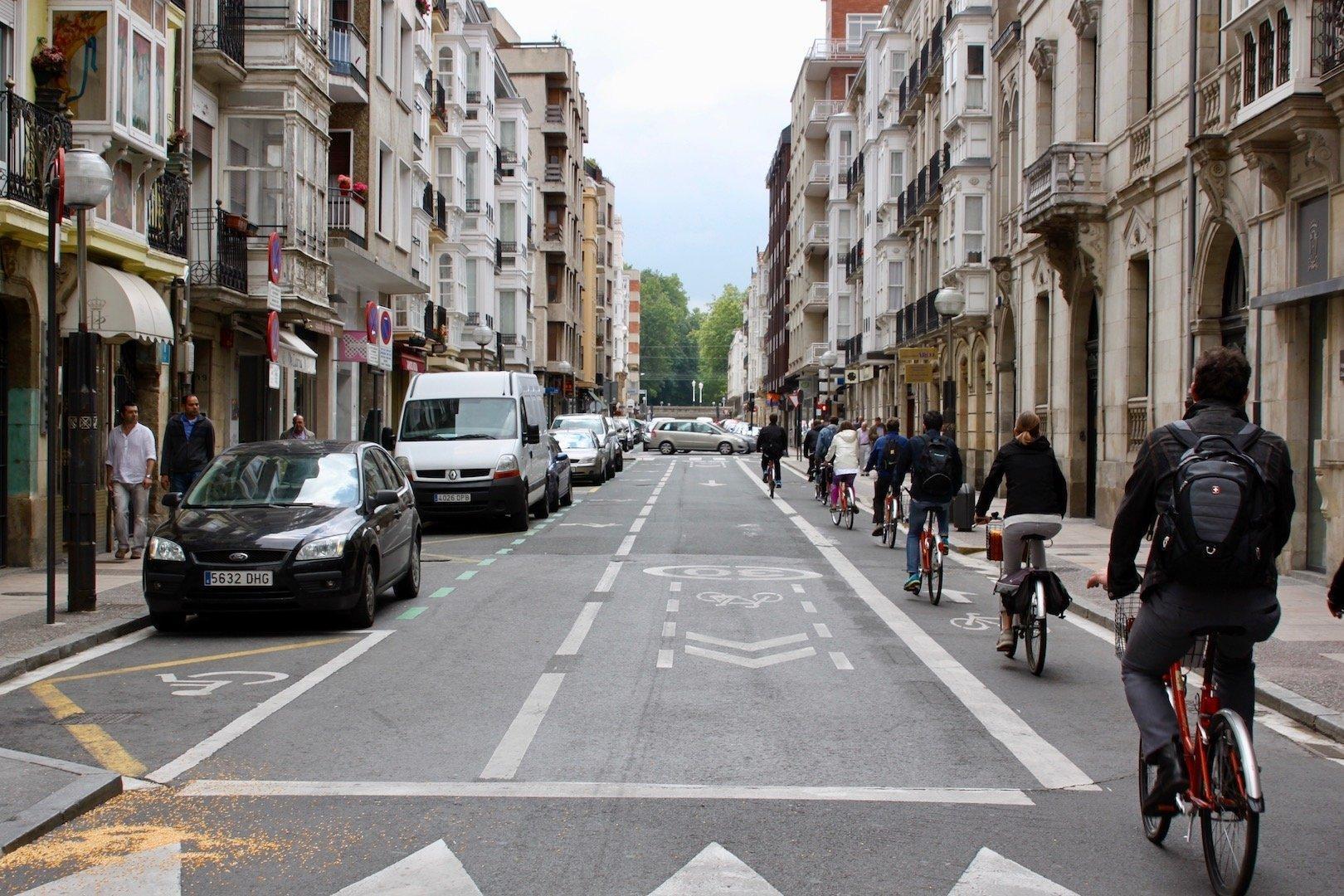 Eine Straße, die zwischen Altbauten verläuft. Radfahrer nutzen ein Teil der rechten Spur, links stehen parkende Autos.