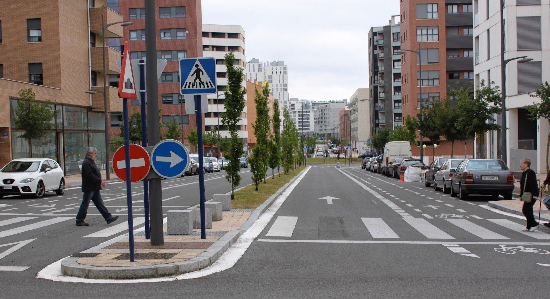 Eine leere Straße. Hochhäuser im Hintergrund.