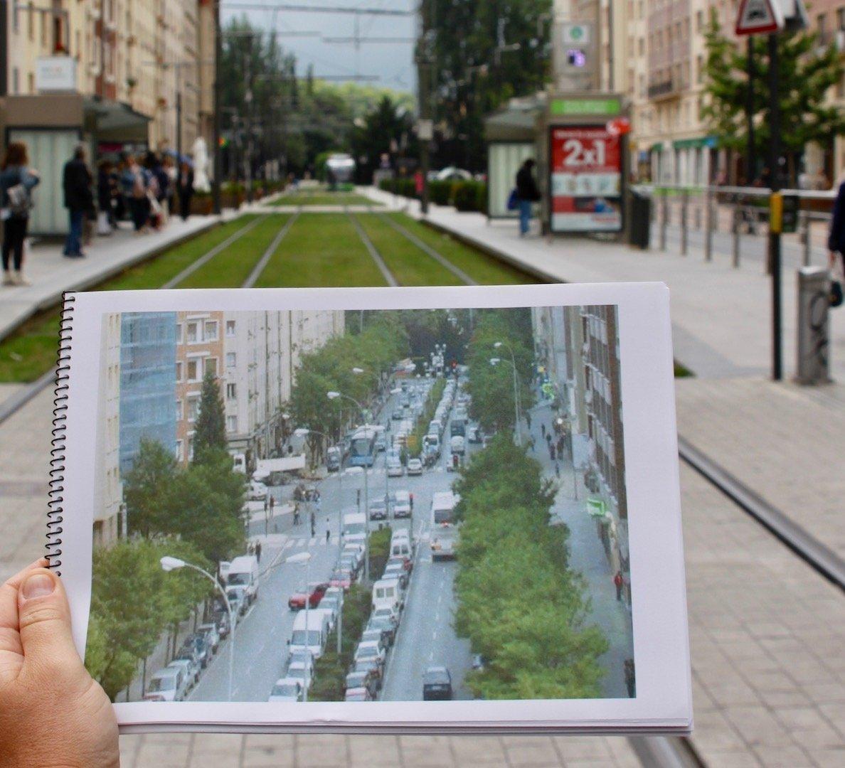 Eine Hand hält einen Block vor der Straße hoch. Auf dem Block ist ein Bild der Teil der Straße aus der Froschperspektive zu sehen.