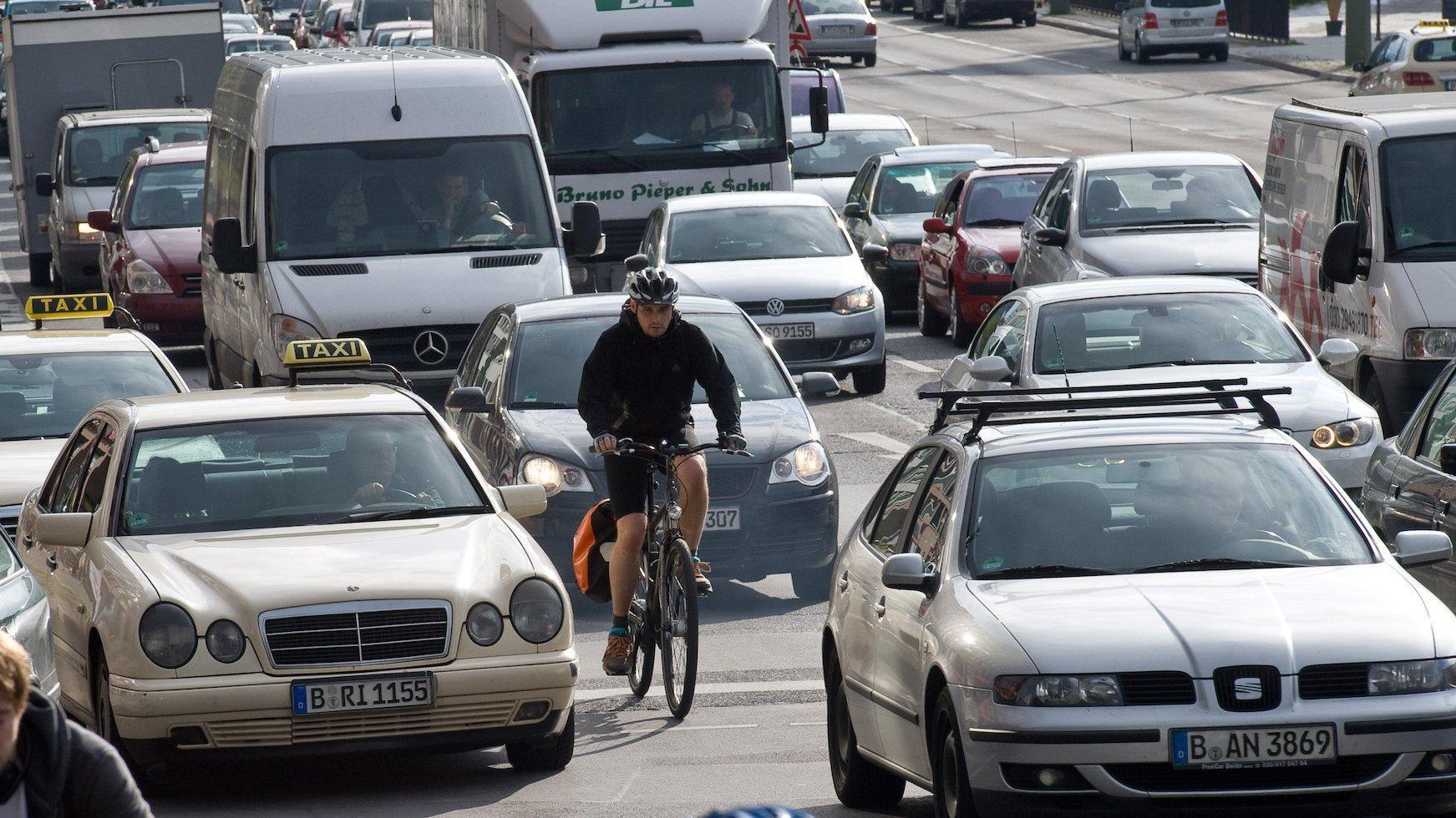 Eine mehrspurige Straße mit Stau. Ein Radfahrer schlängelt sich durch die Fahrzeuge.